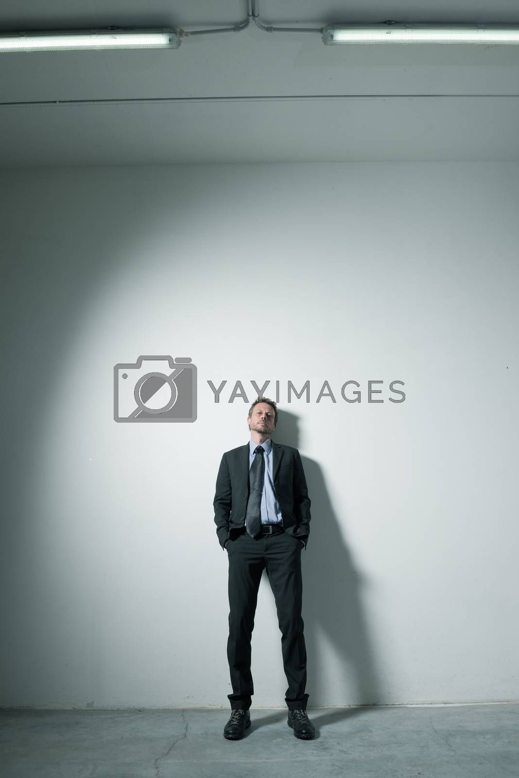 Businessman leaning on a wall by stokkete
