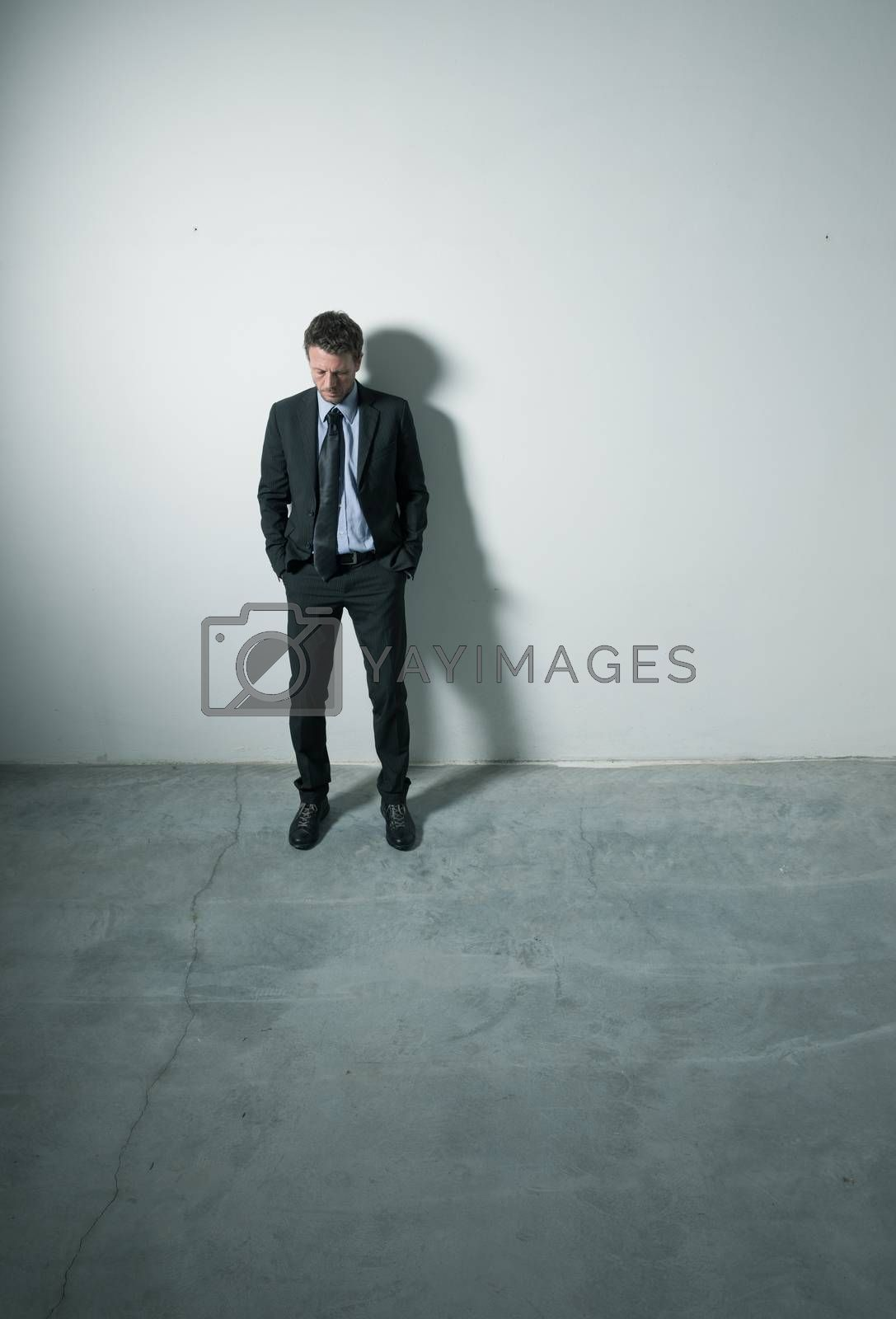 Tired pensive businessman standing with hands in pockets in an empty room with dramatic lighting.