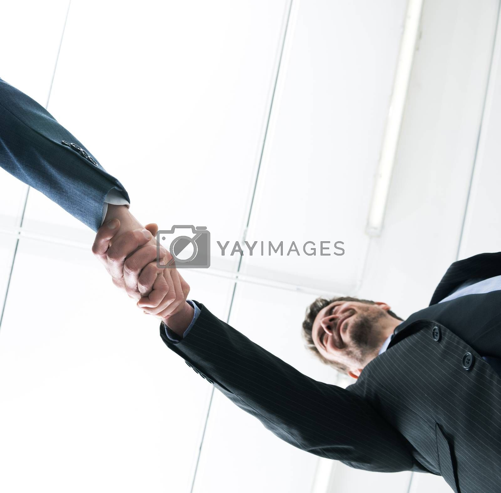 Confident young businessmen smiling and shaking hands bottom view.