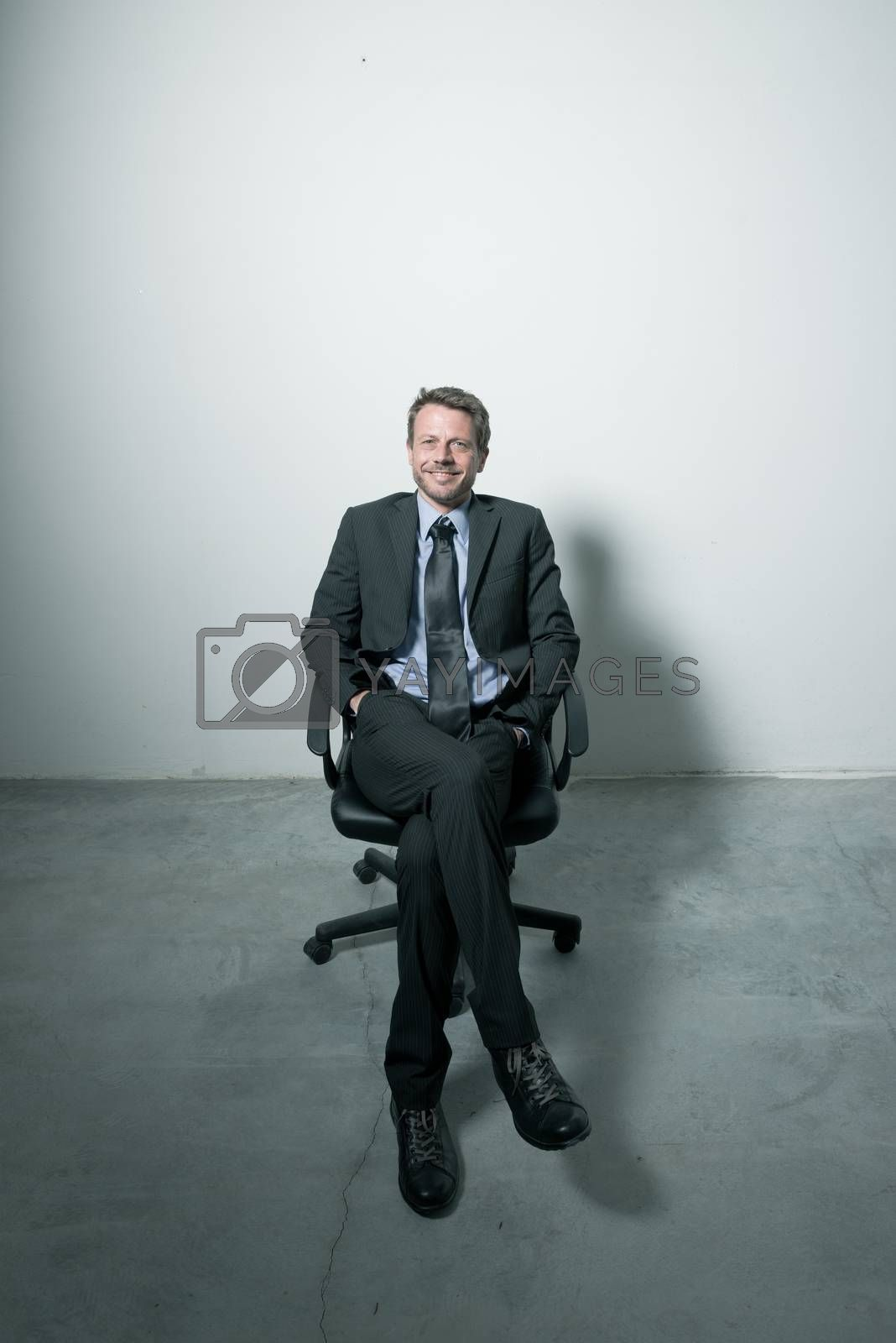 Businessman sitting on an office chair by stokkete