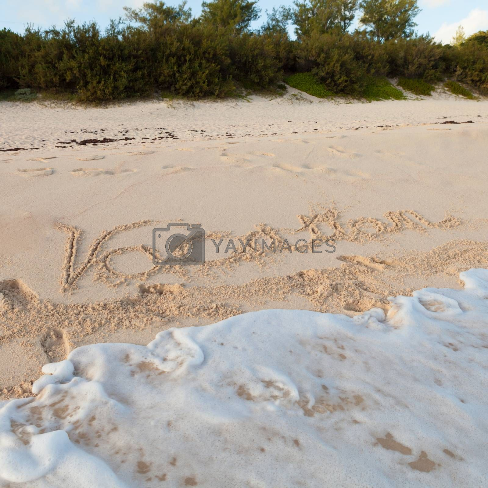 The word Vacation written in the sand on a Bermuda beach with pink sands.