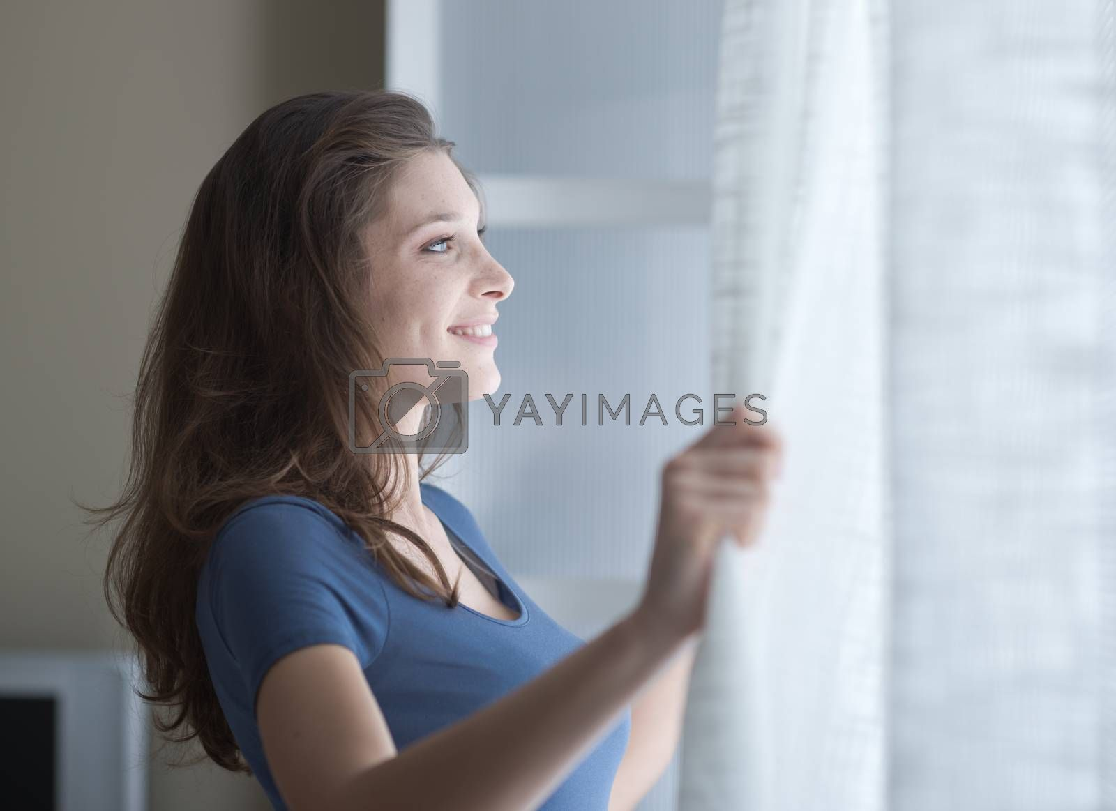 A young woman looking through her window early in the morning