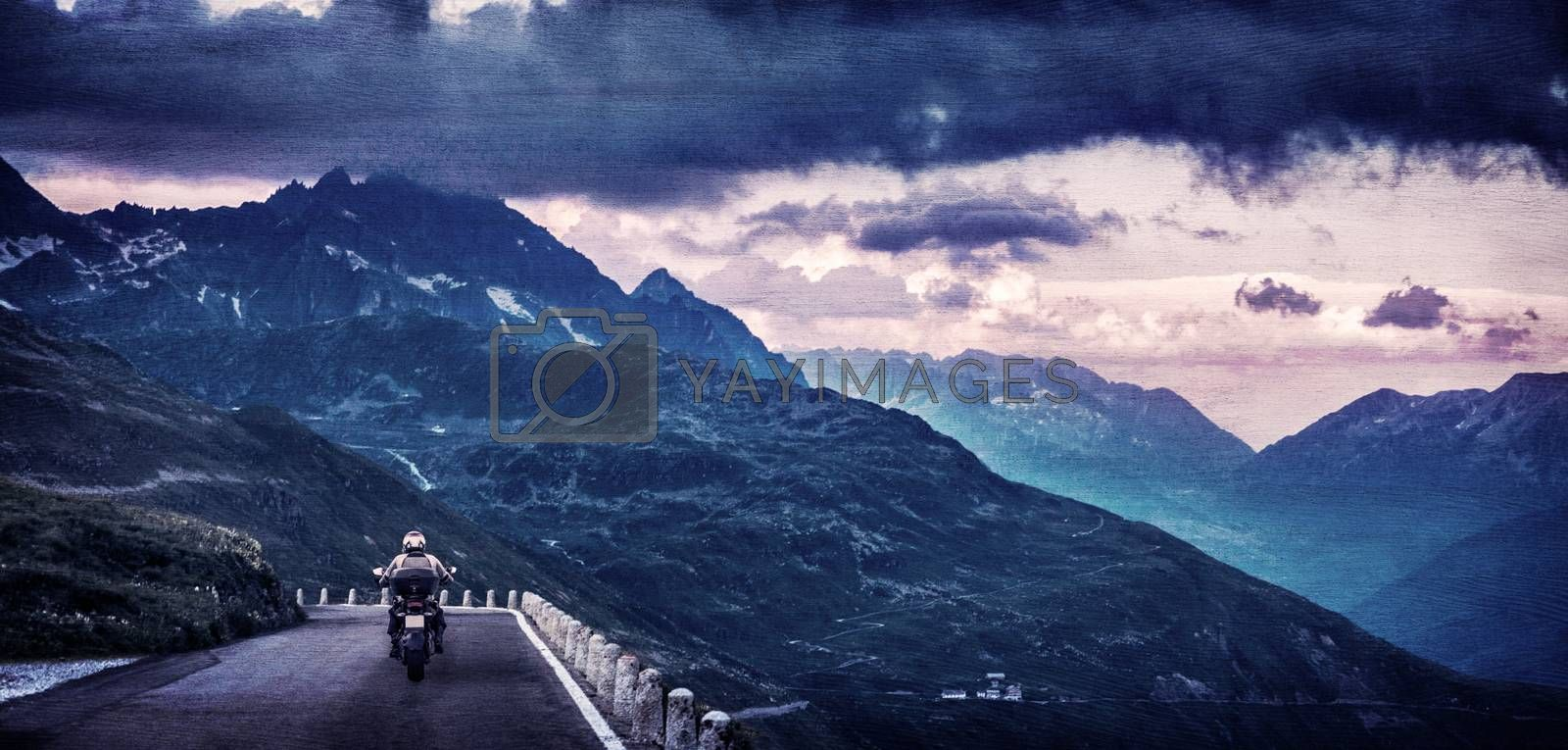 Grunge style photo of motorcyclist on mountainous highway, riding in the evening in overcast weather, traveling along European mountains