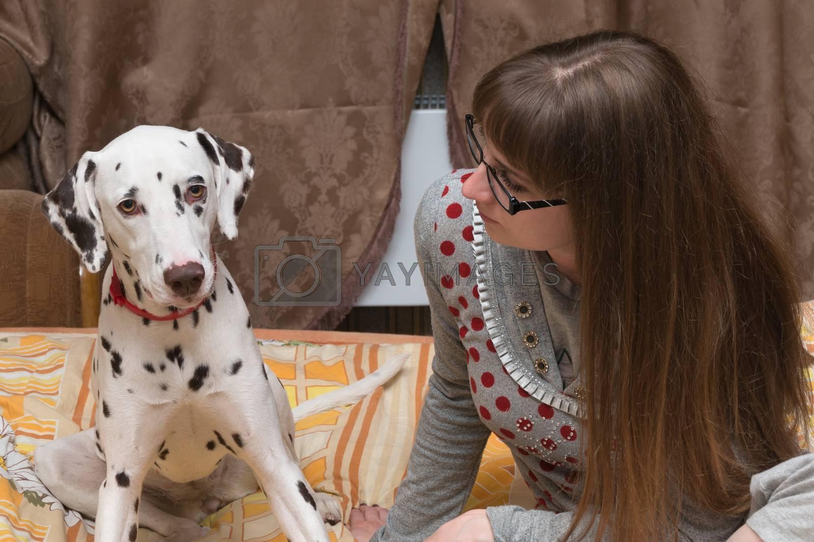 The girl talks to a dalmatian