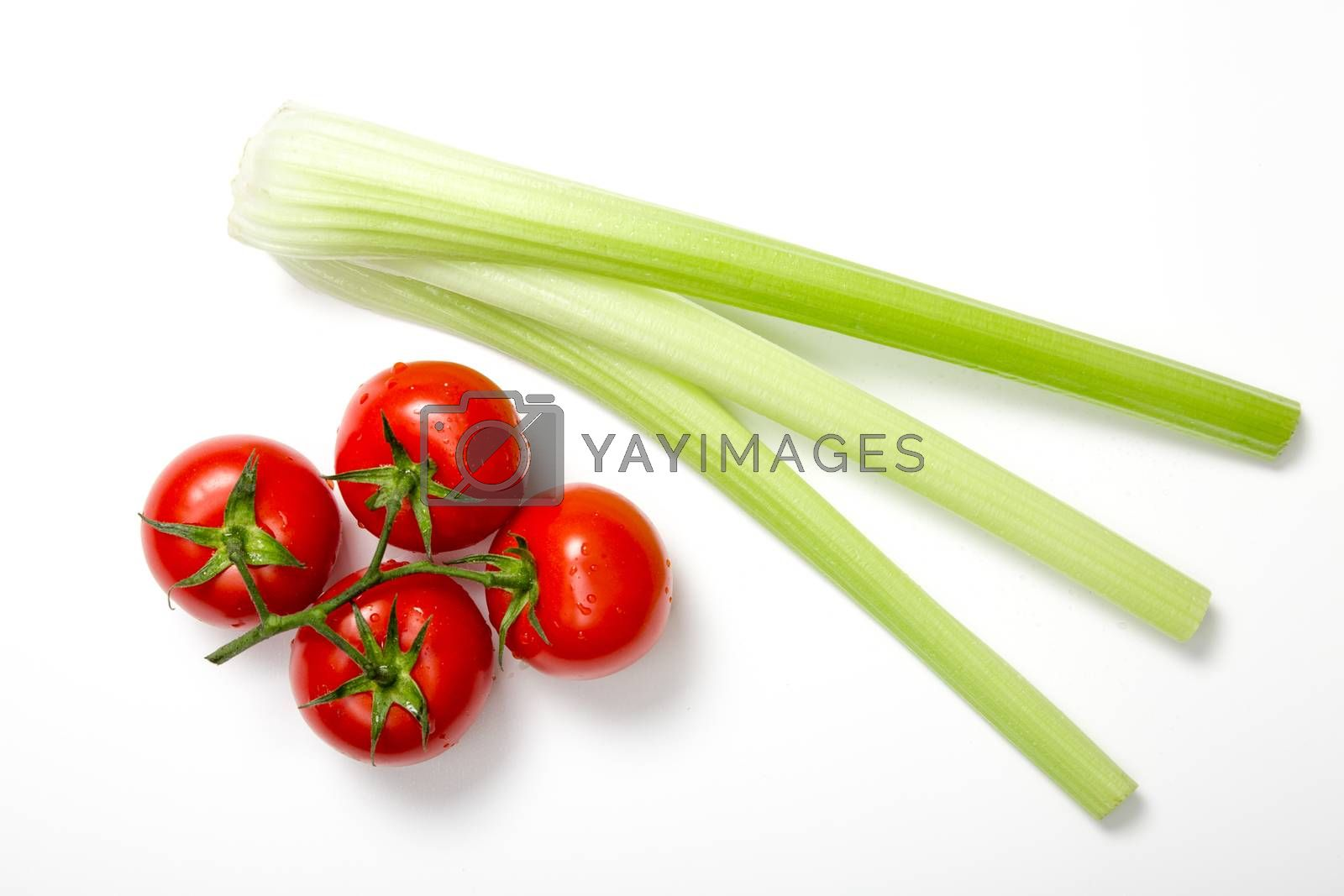 Top view of bunch of fresh tomatoes and celery sticks on white background