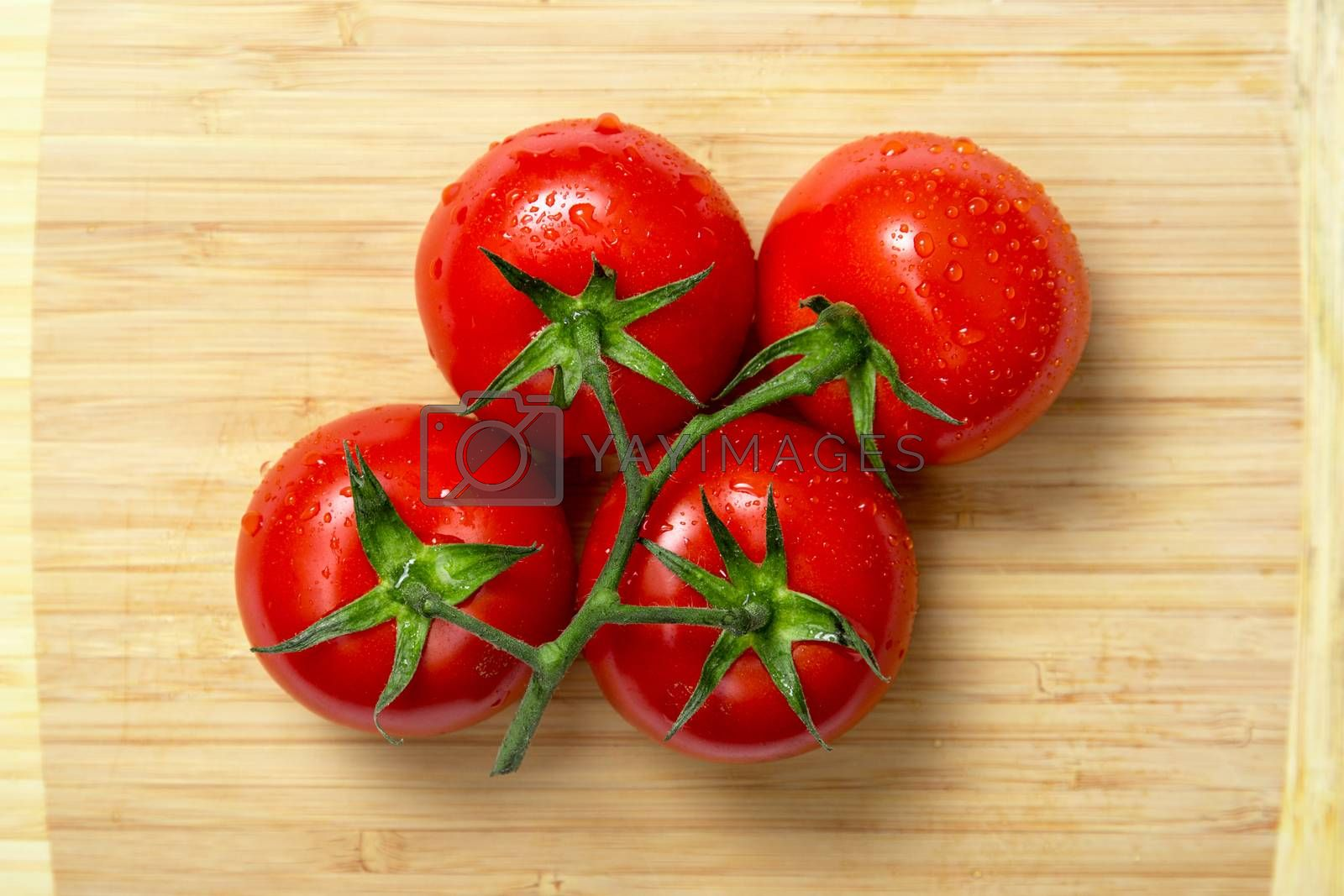 Top view of fresh tomatoes on wooden chopping board