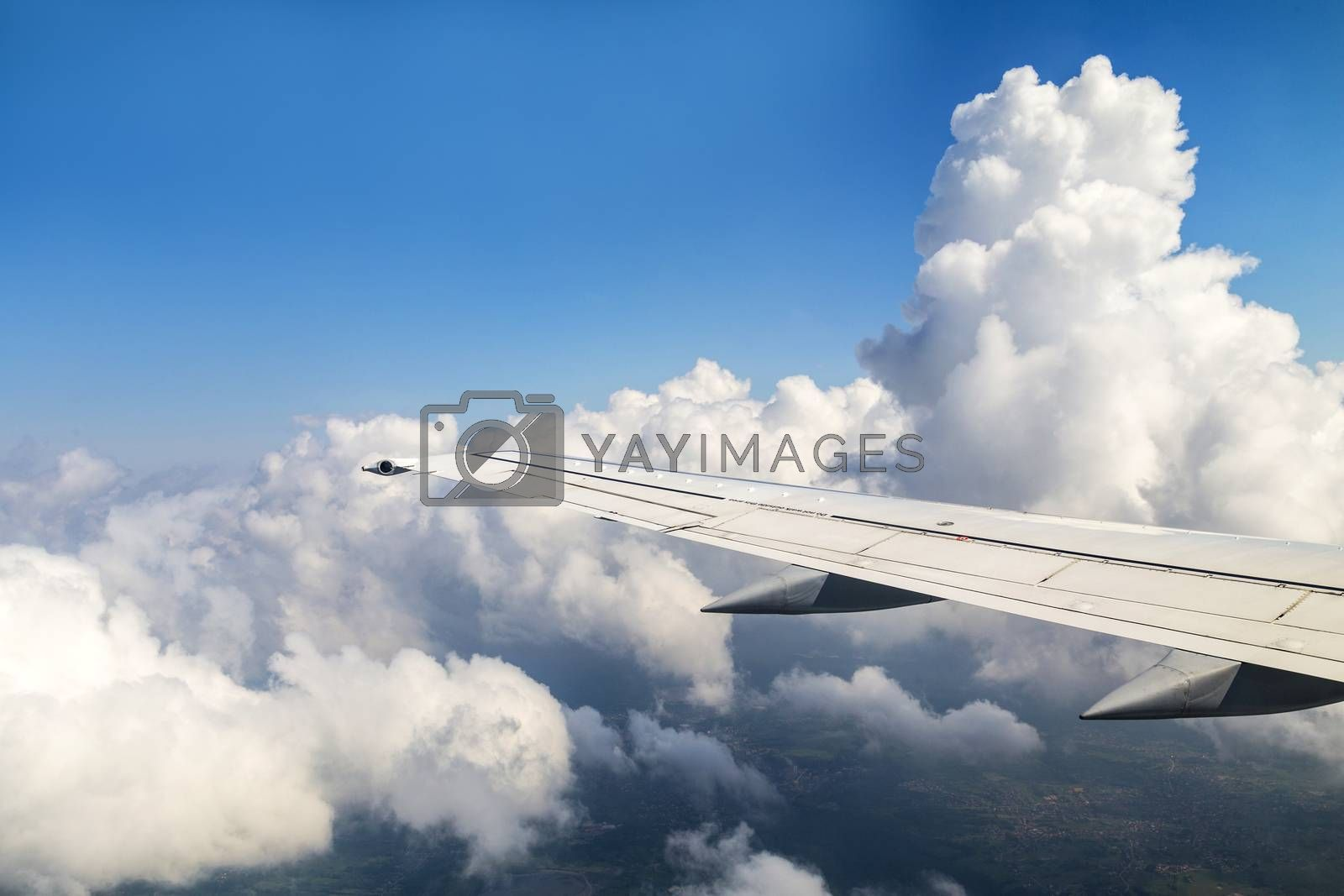 Wing of an airplane flying above the clouds by meinzahn