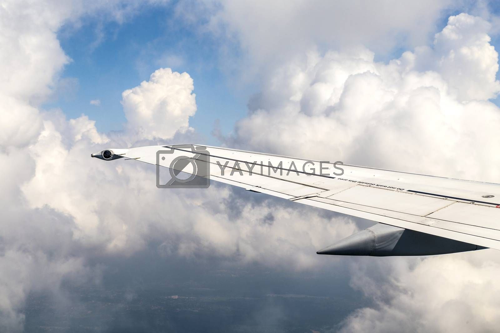 Royalty free image of Wing of an airplane flying above the clouds by meinzahn