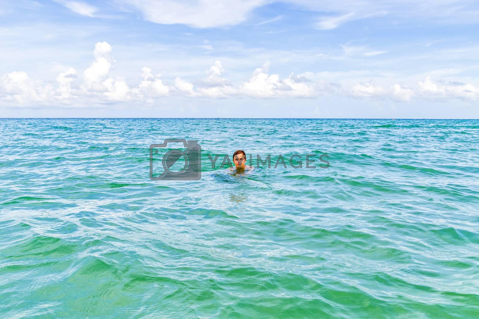 teenage boy enjoys breaststroking in the ocean