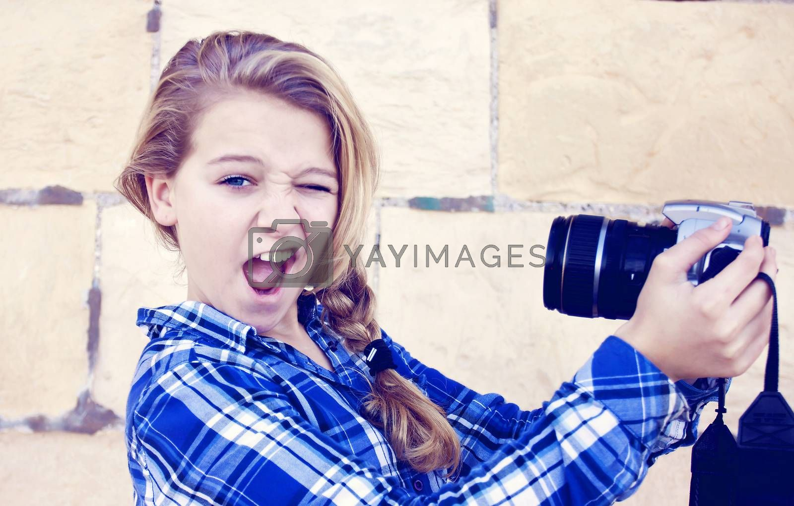 Young teenage girl doing a funny face taking a self portrait with a slr camera. Slight retro tint over image