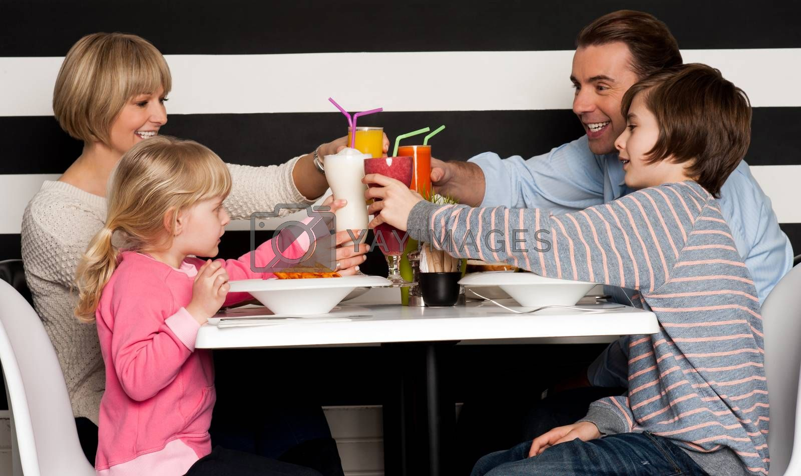 Family toasting smoothies in restaurant by stockyimages