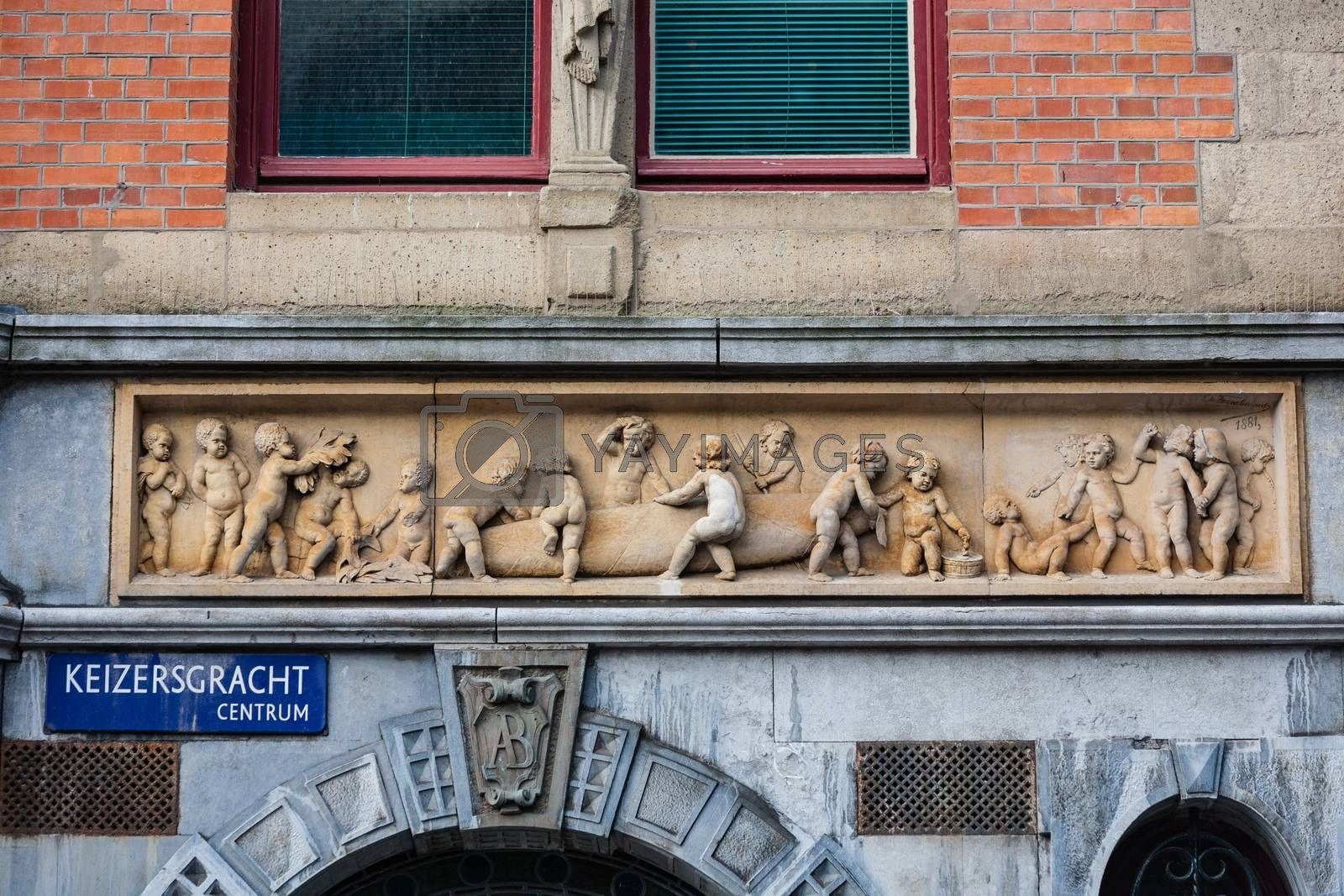 Haut-relief in Amsterdam street with a very funny group of children elaborating a cigar