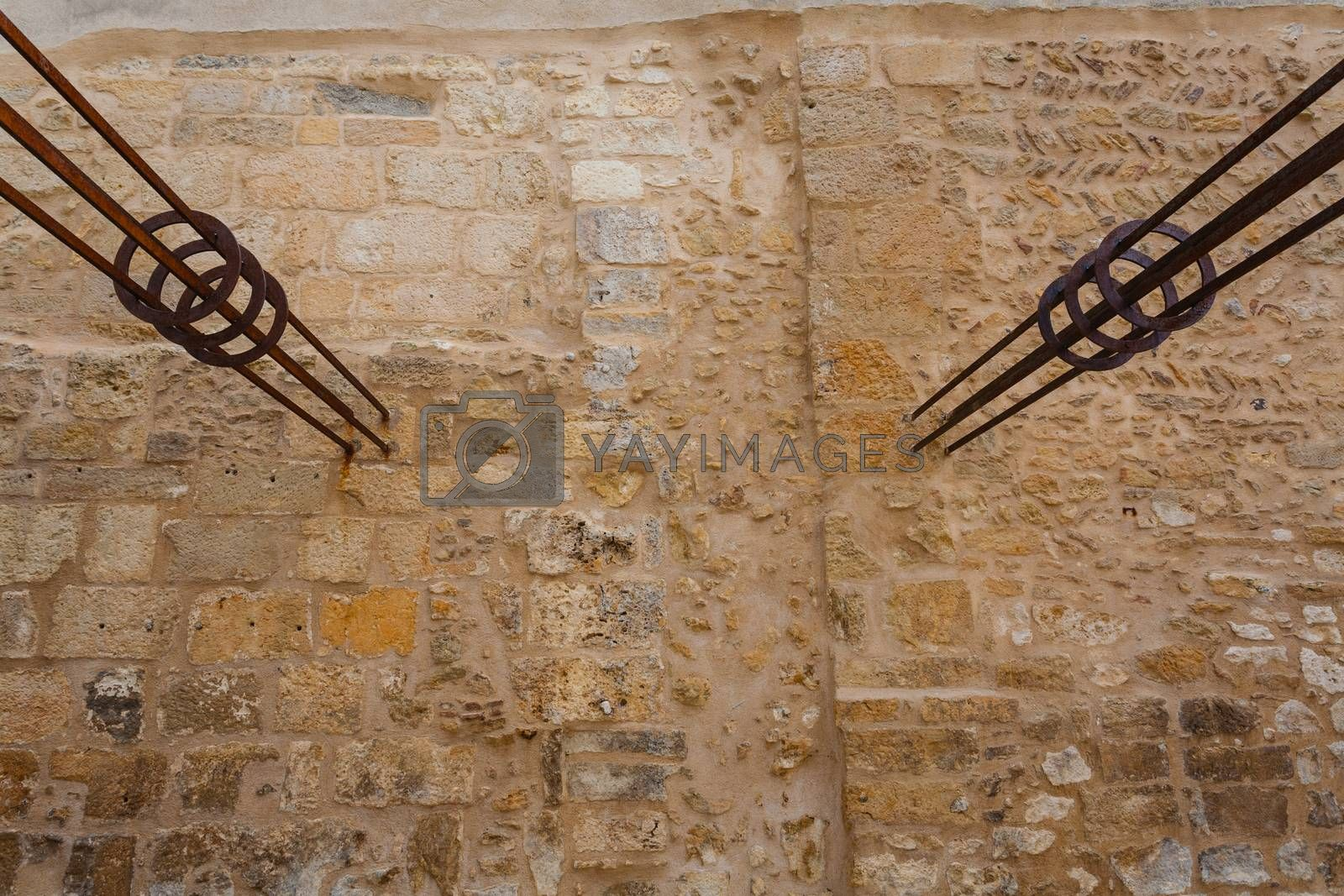 Two forged pieces of iron hammered in a stoned wall in a park in the city of Perigueux in France