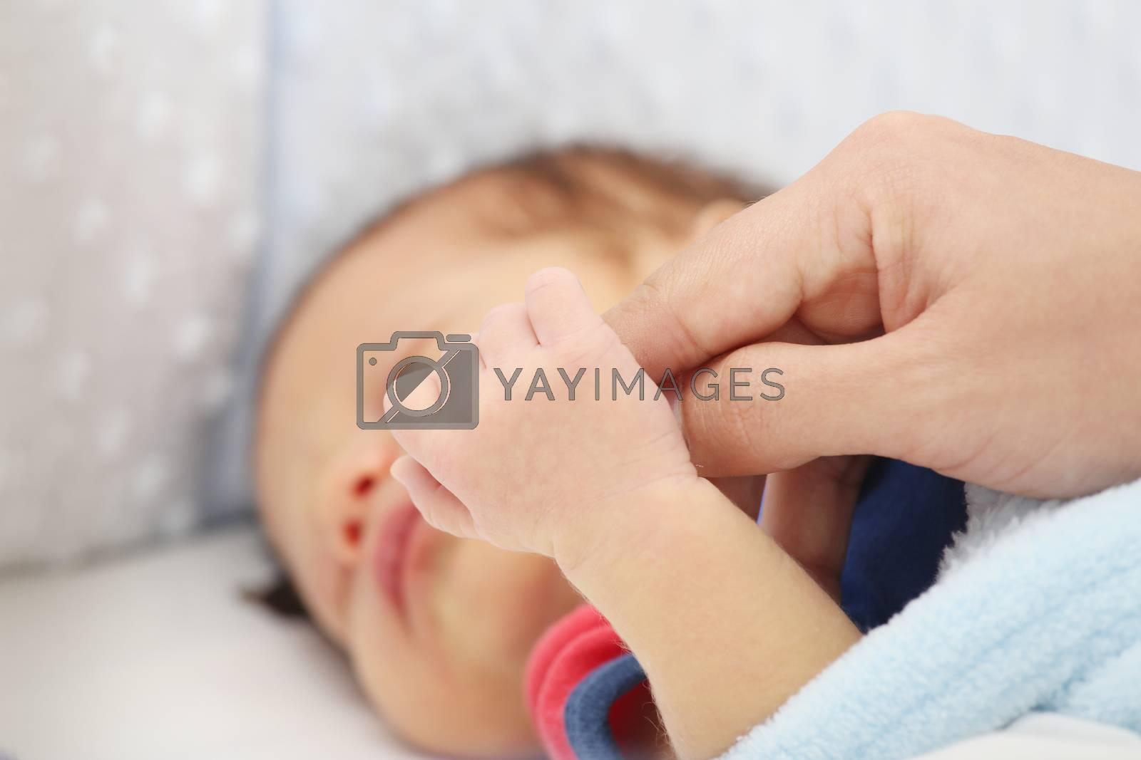 Slept baby hand holding mother finger