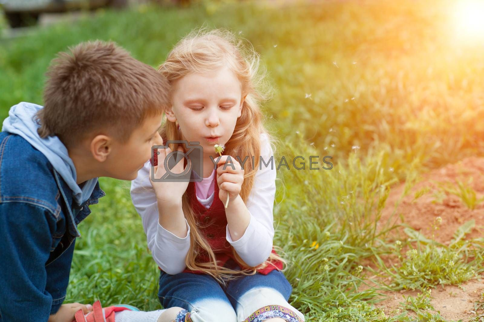 girl and boy blow on dandelion