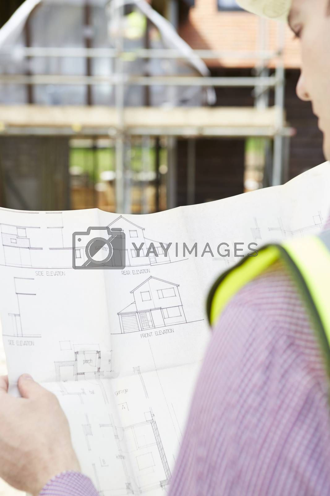 Architect On Building Site Looking At Plans For House