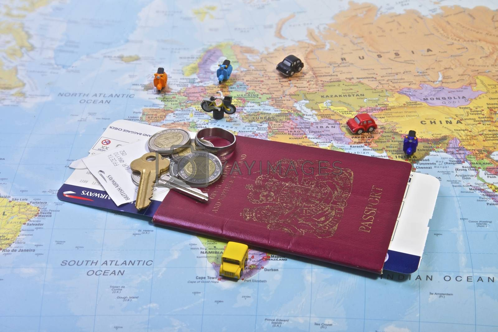 British Passport flight ticket and personal belongings displayed on a world map. Travel and vacation