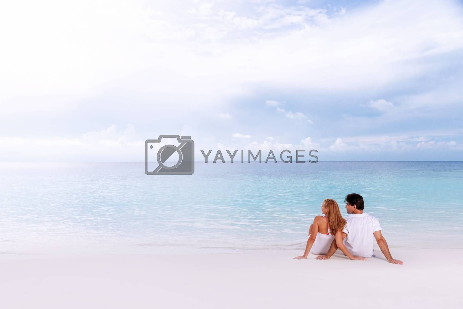 Rear view of loving couple relaxing on the beach, boyfriend with girlfriend enjoying summer holidays on luxury Maldives resort, love and romance concept