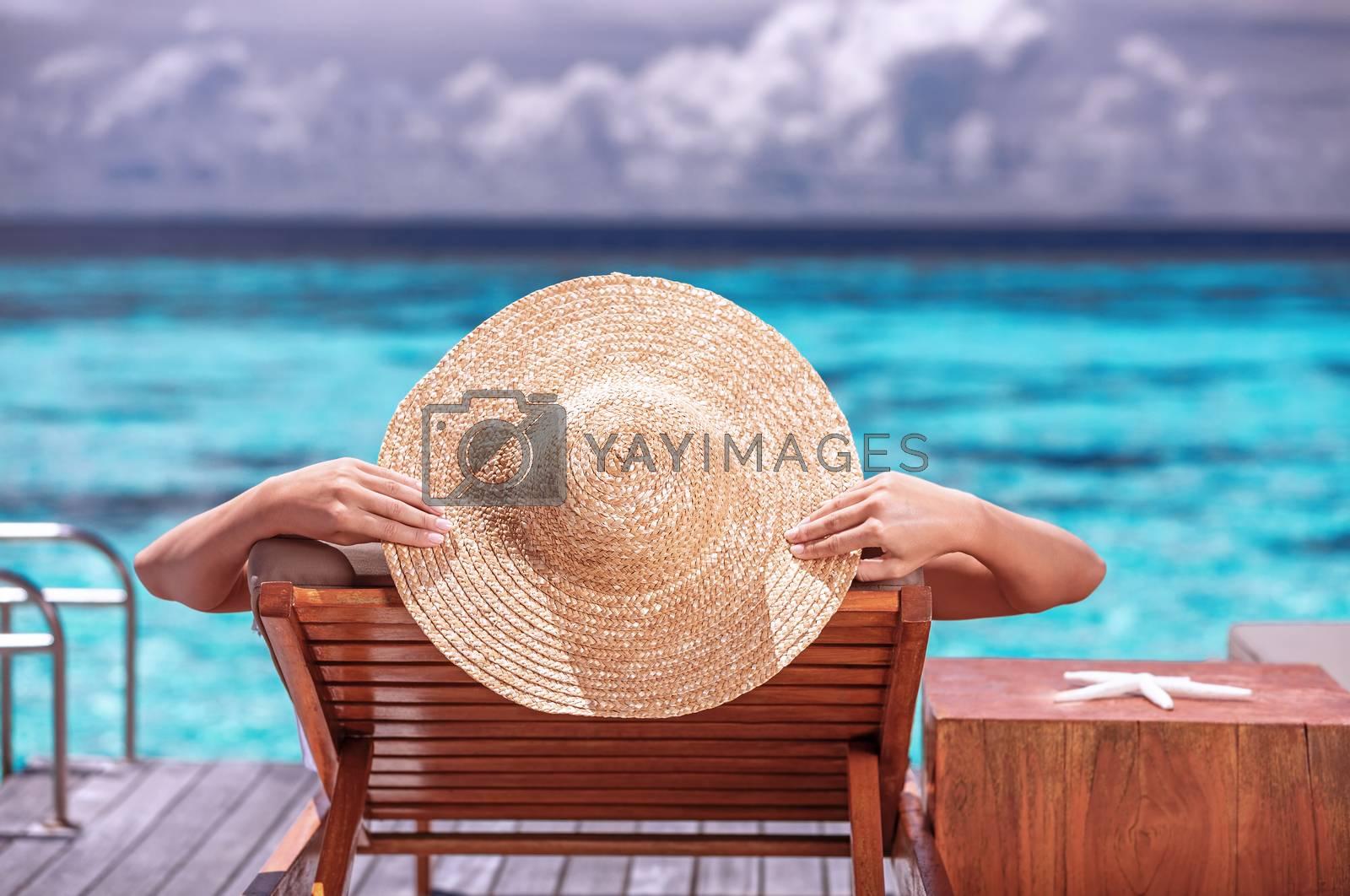 Luxury female tanning on the beach, wearing big stylish hat, enjoying beautiful seascape, summer travel and tourism concept