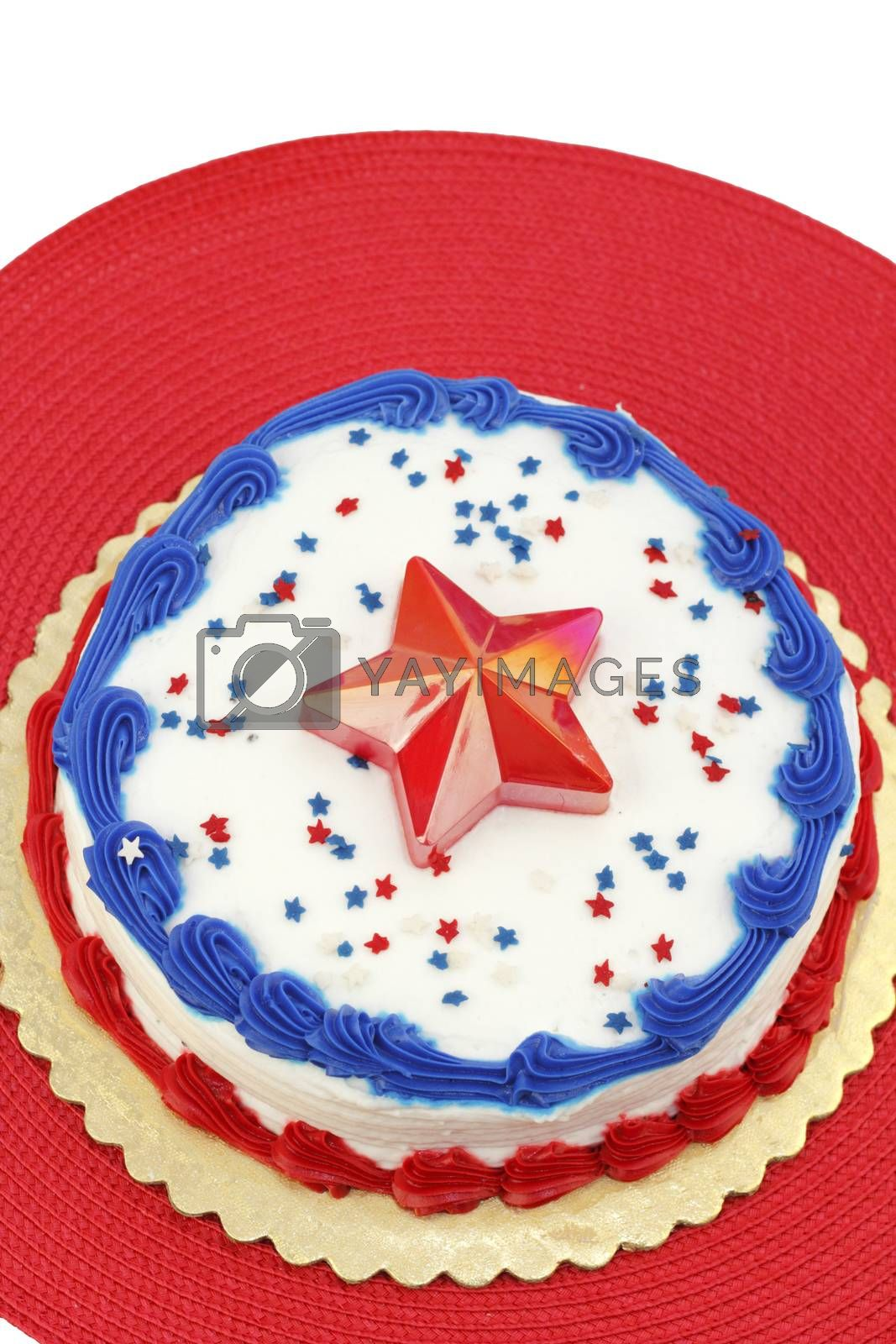 Festive red, white and blue July 4th cake, decorated with edible star sprinkles, one large plastic star, and frosting. The dessert is placed on a gold foundation over a round red place mat.