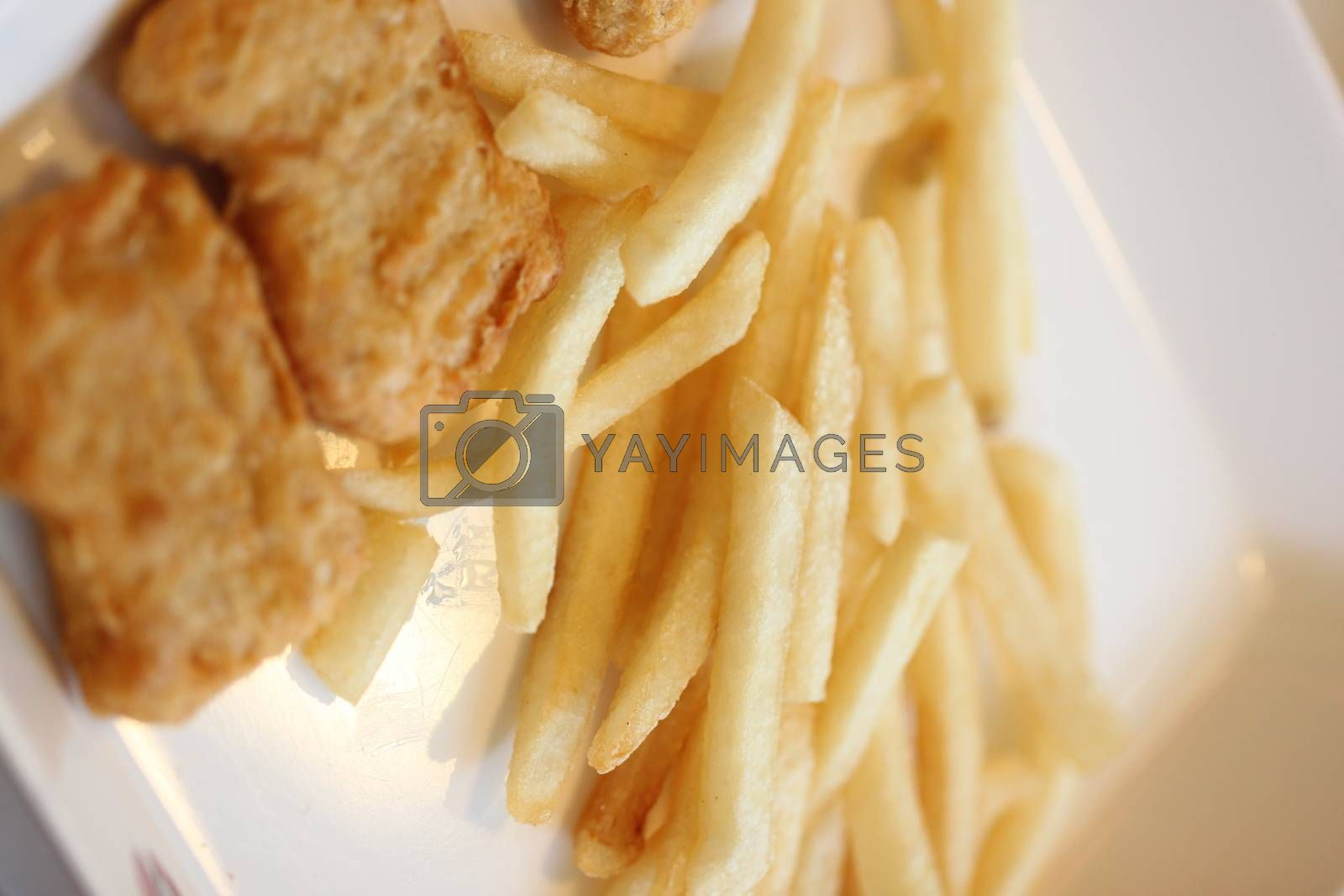 French fries and fried chicken on dish. by PiyaPhoto