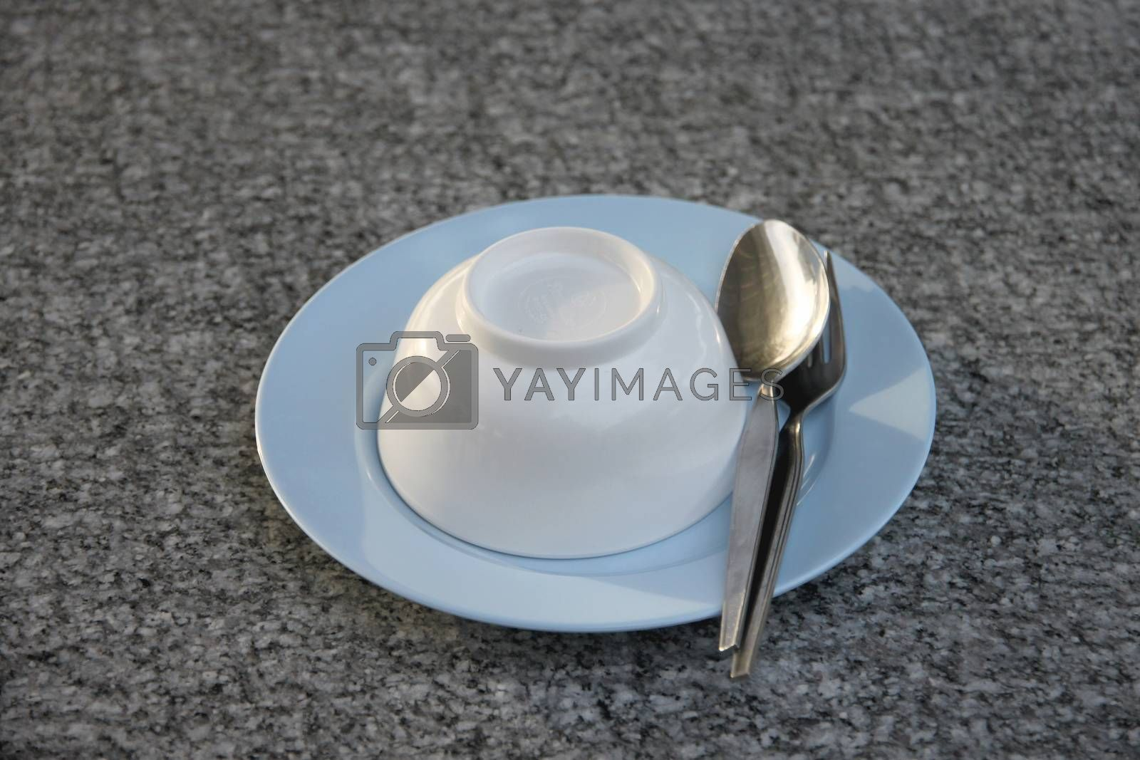 Plate and spoon on table. by PiyaPhoto