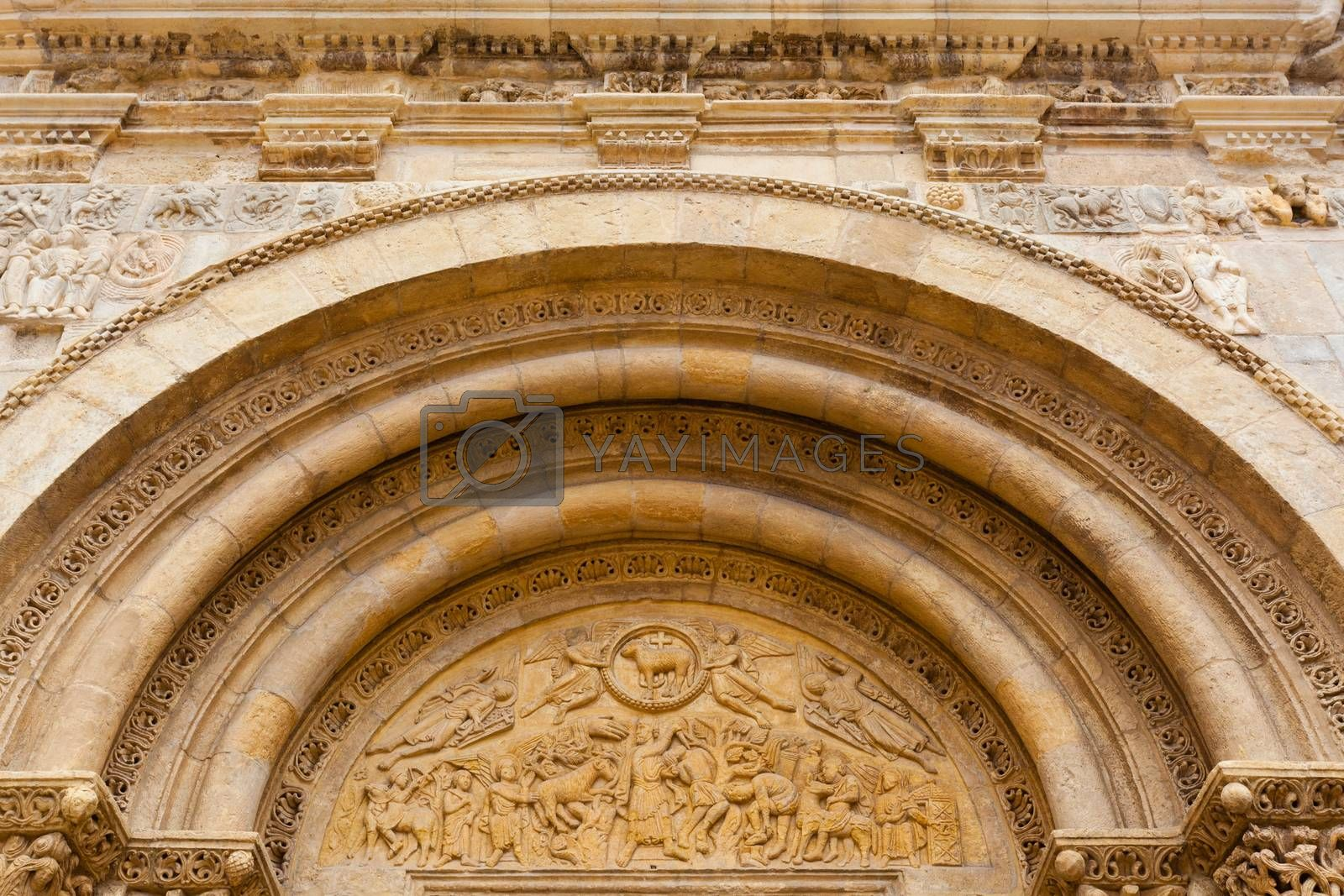 Closeup view of romanesque arhivolts and carved tympanum in the main entrance door of the San Isidoro Collegiate church in Leon, Spain