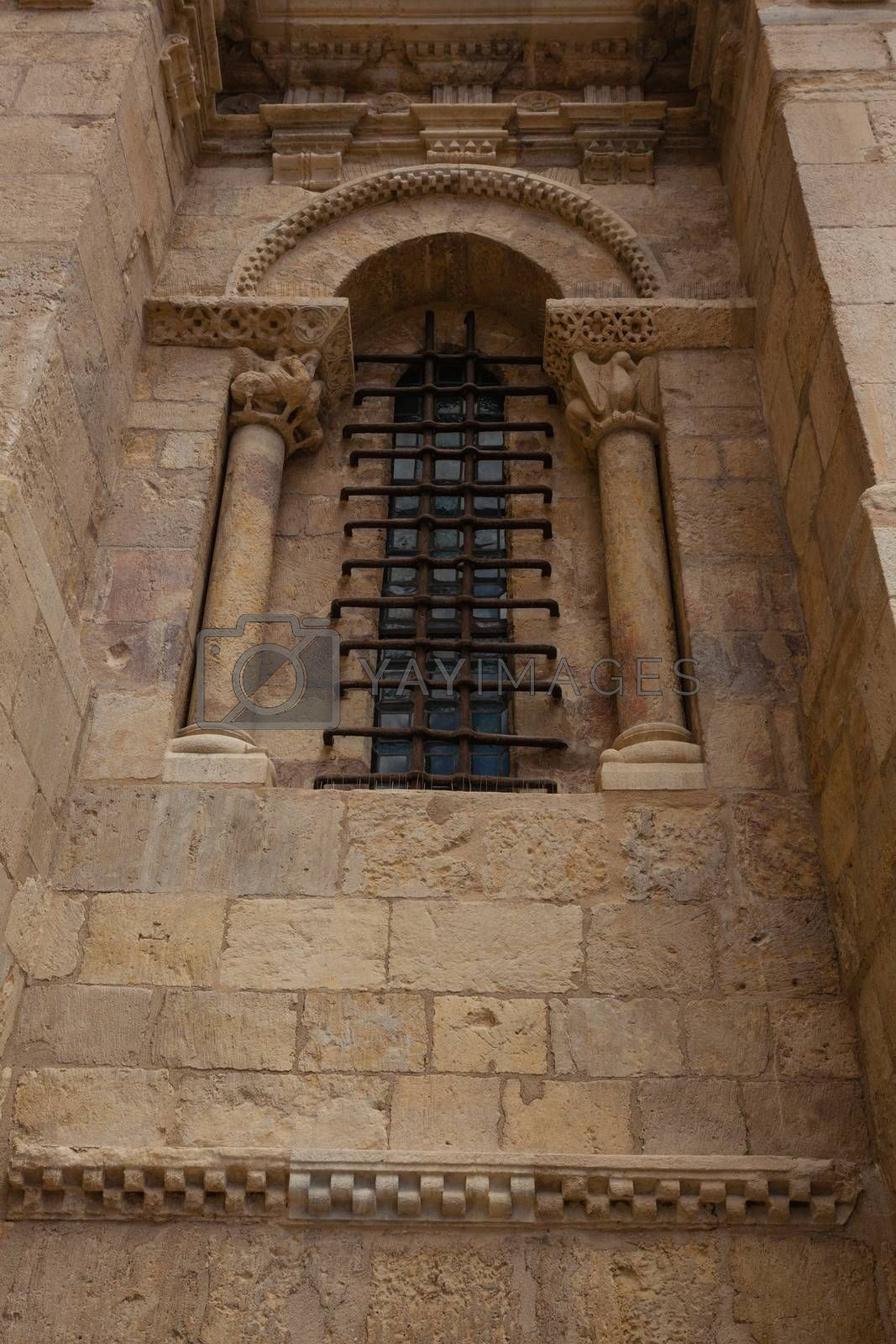 Lateral small fine window in the romanesque collegiate of San Isidoro ,province of Leon in Spain