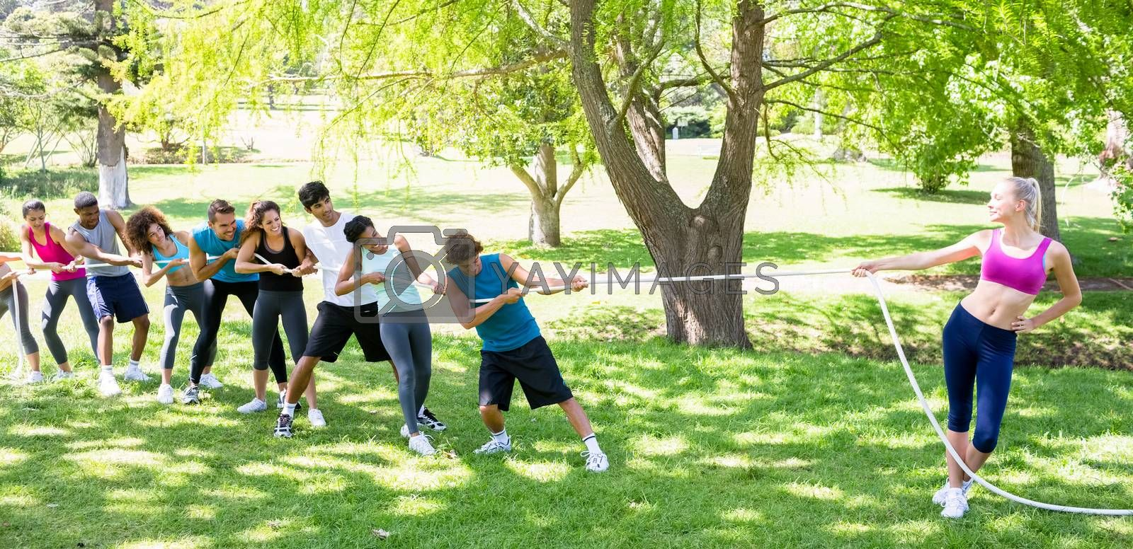 Fit woman playing tug of war with group of friends in the park