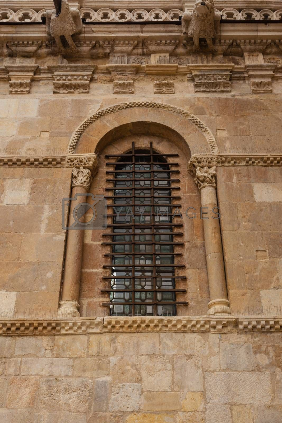 Excellent piece of romanesque art window with fine forged protection in the side wall of the San Isidoro collegiate church in Leon ,Spain