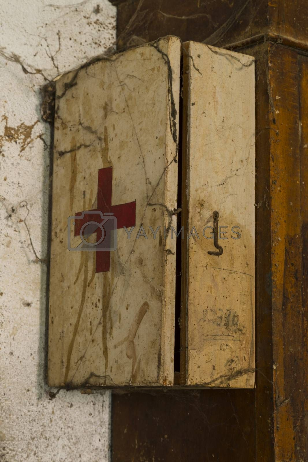 An old first aid kit on a dirty and rusty wall covered by cobwebs