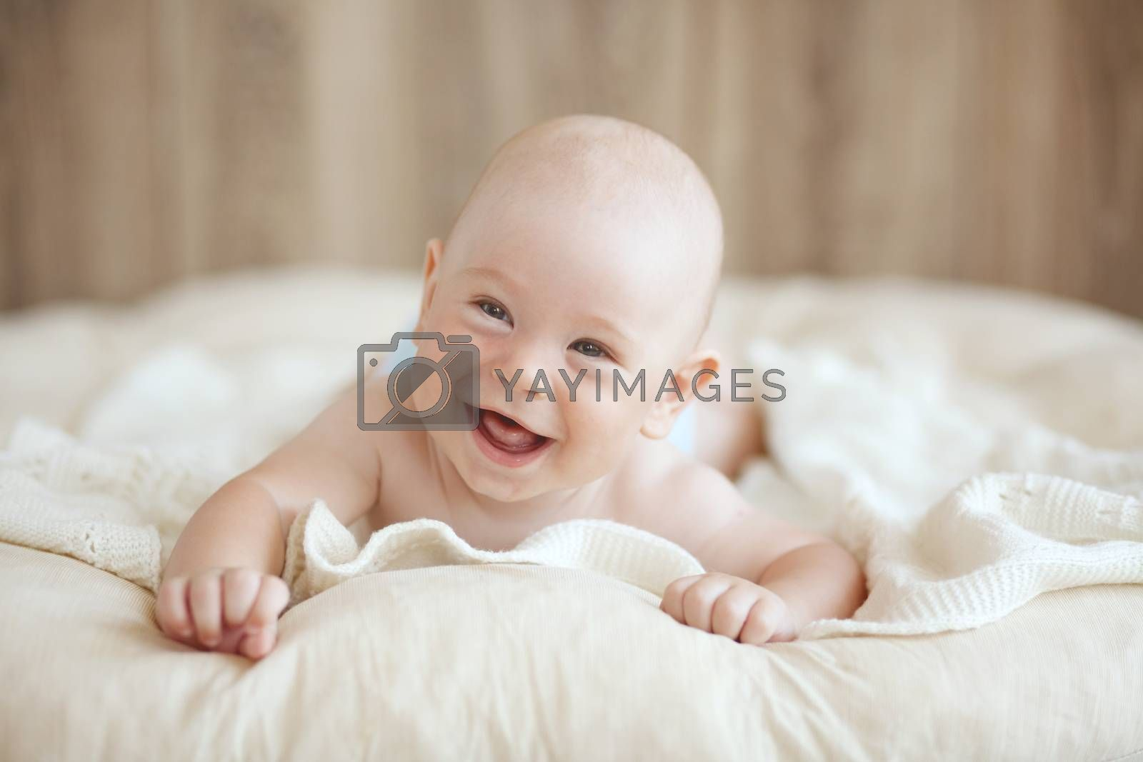 Portrait of a cute 4 months baby lying down on a blanket