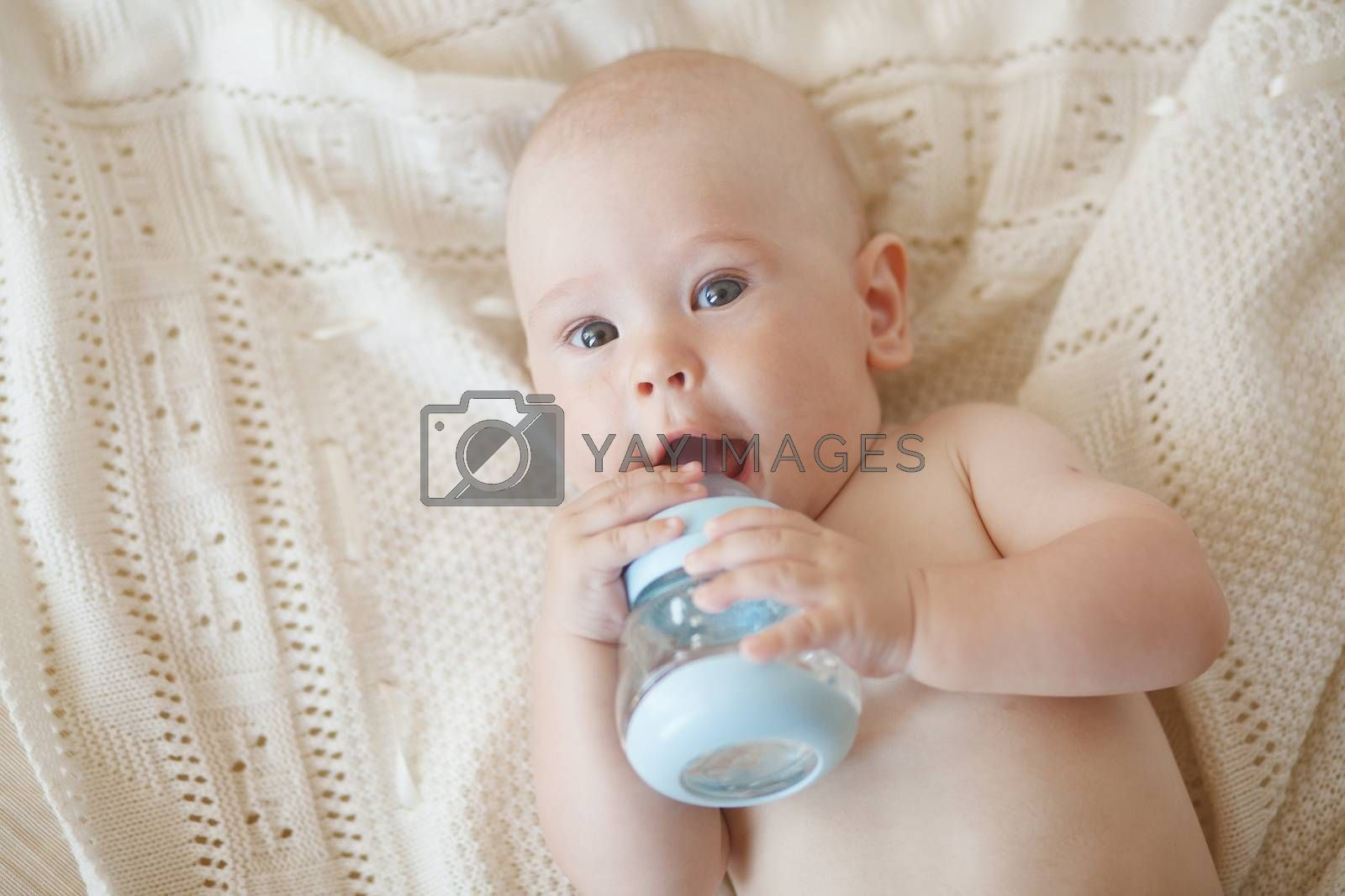 Portrait of a cute 4 months baby drinking water from bottle top view