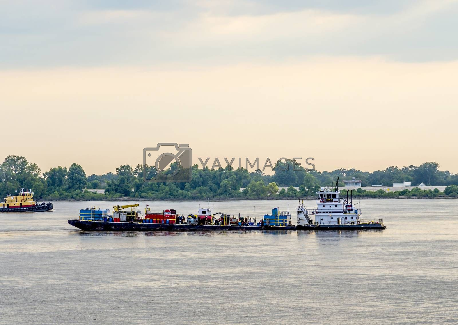 BATON ROUGE, USA - JULY 13, 2013: freight ship on Mississippi river at sunset in Baton Rouge, USA. The Mississippi ranks as the fourth longest and tenth largest river in the world.