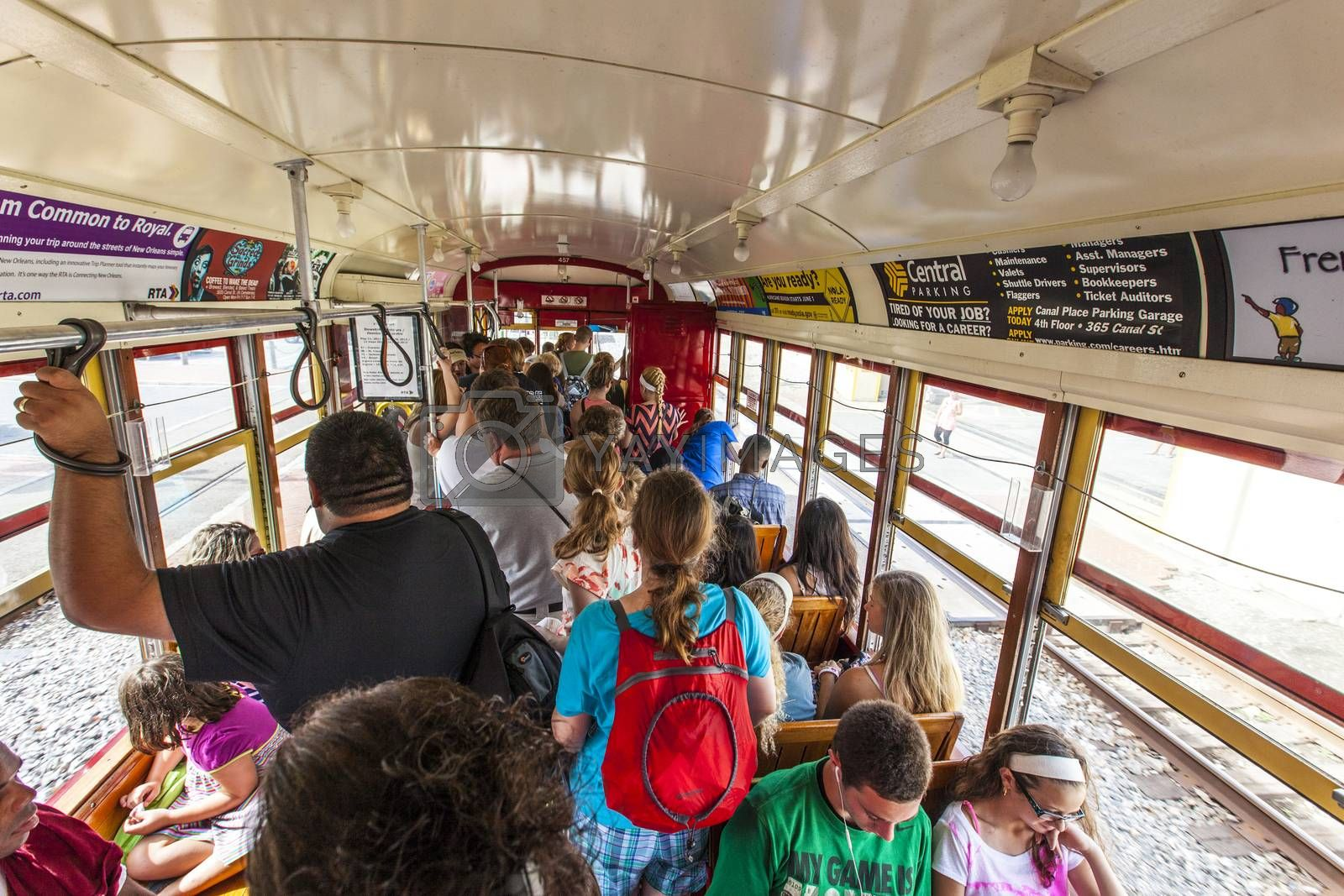 NEW ORLEANS, USA - JULY 16, 2013: people ride in the riverfront  Streetcar Line in New Orleans, USA. Revamped after Hurricane Katrina in 2005, the New Orleans Streetcar line began electric operation in 1893.