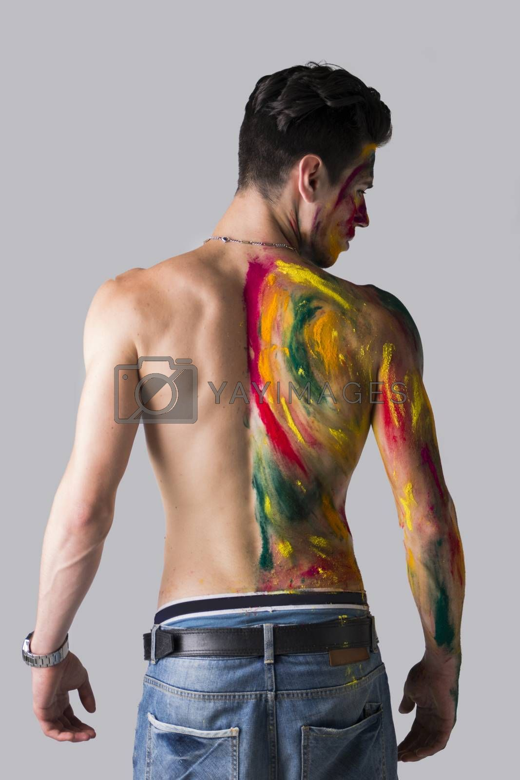 Handsome young man seen from the back with skin all painted with holi colors