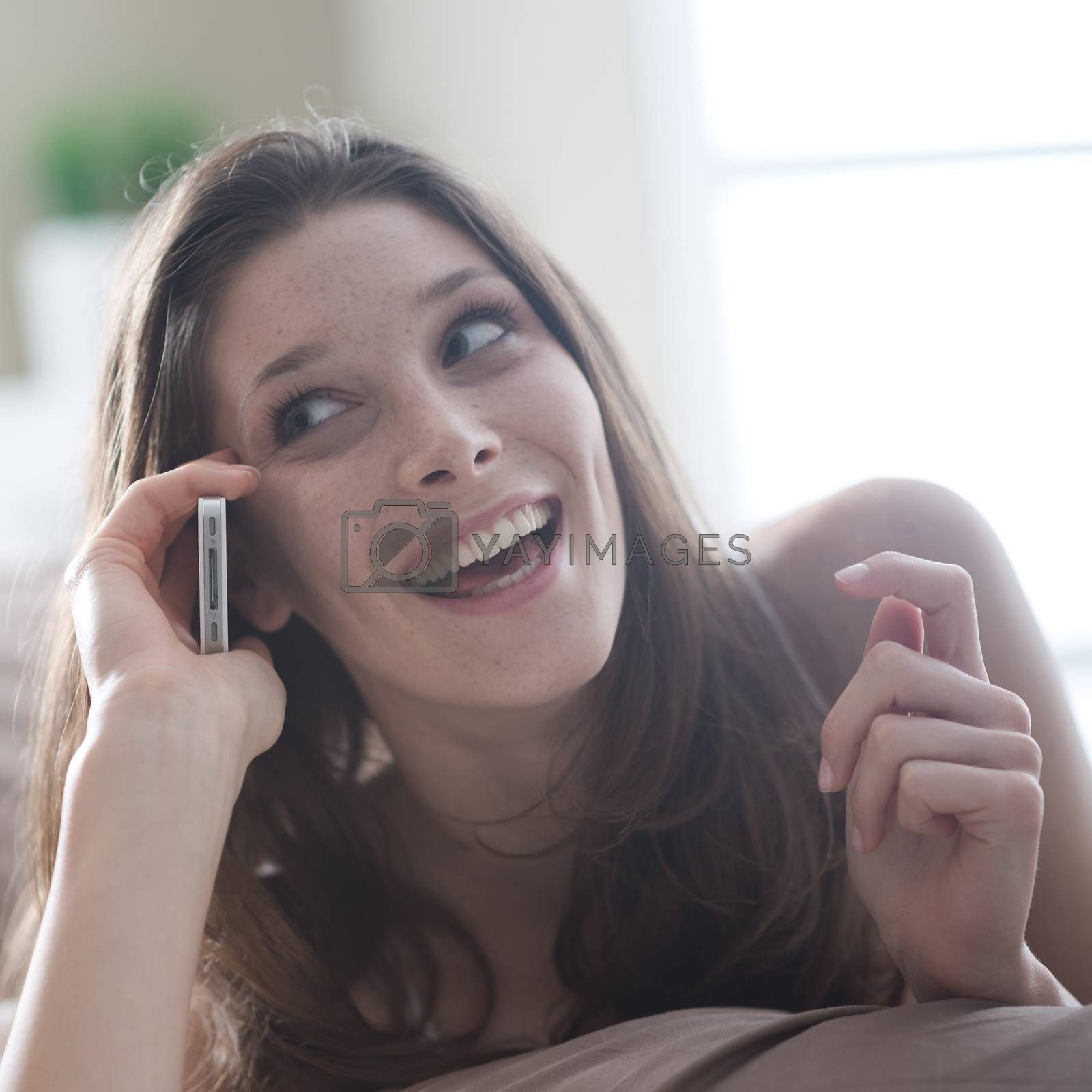 Happy young woman talking on the phone while in bed