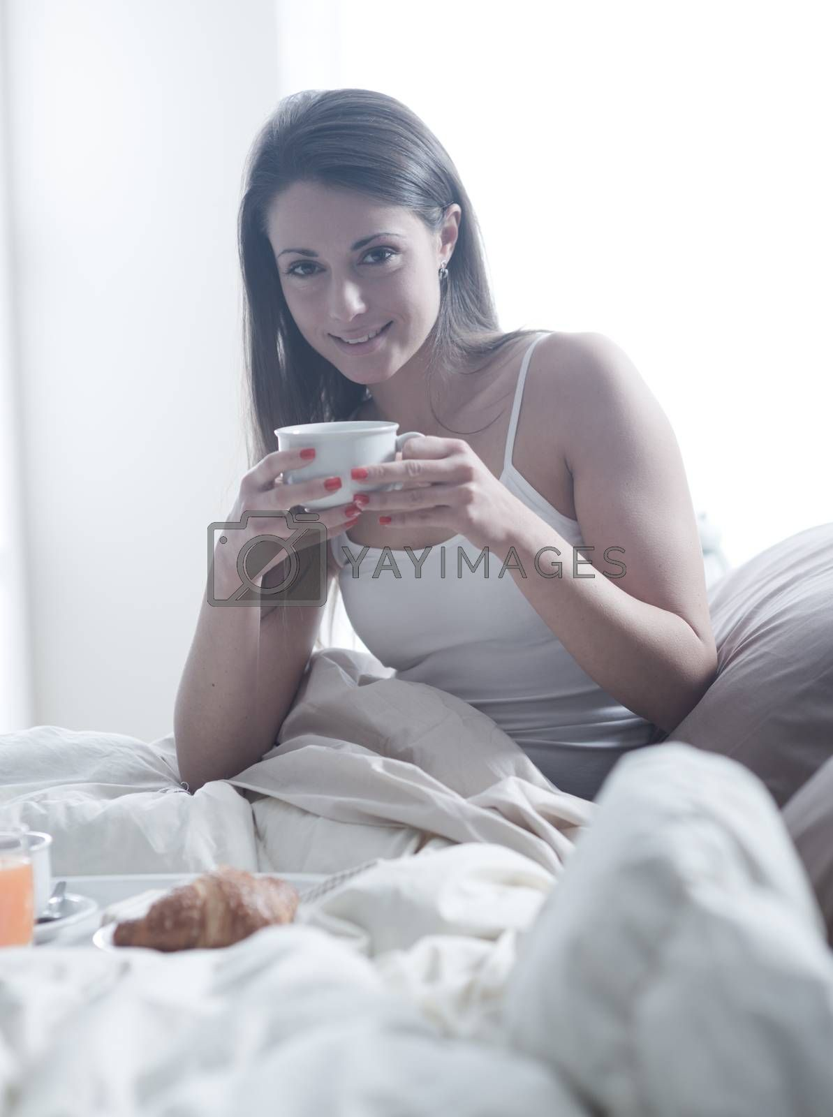 Lovely young woman lying with a cup of coffee and a tray of breakfast