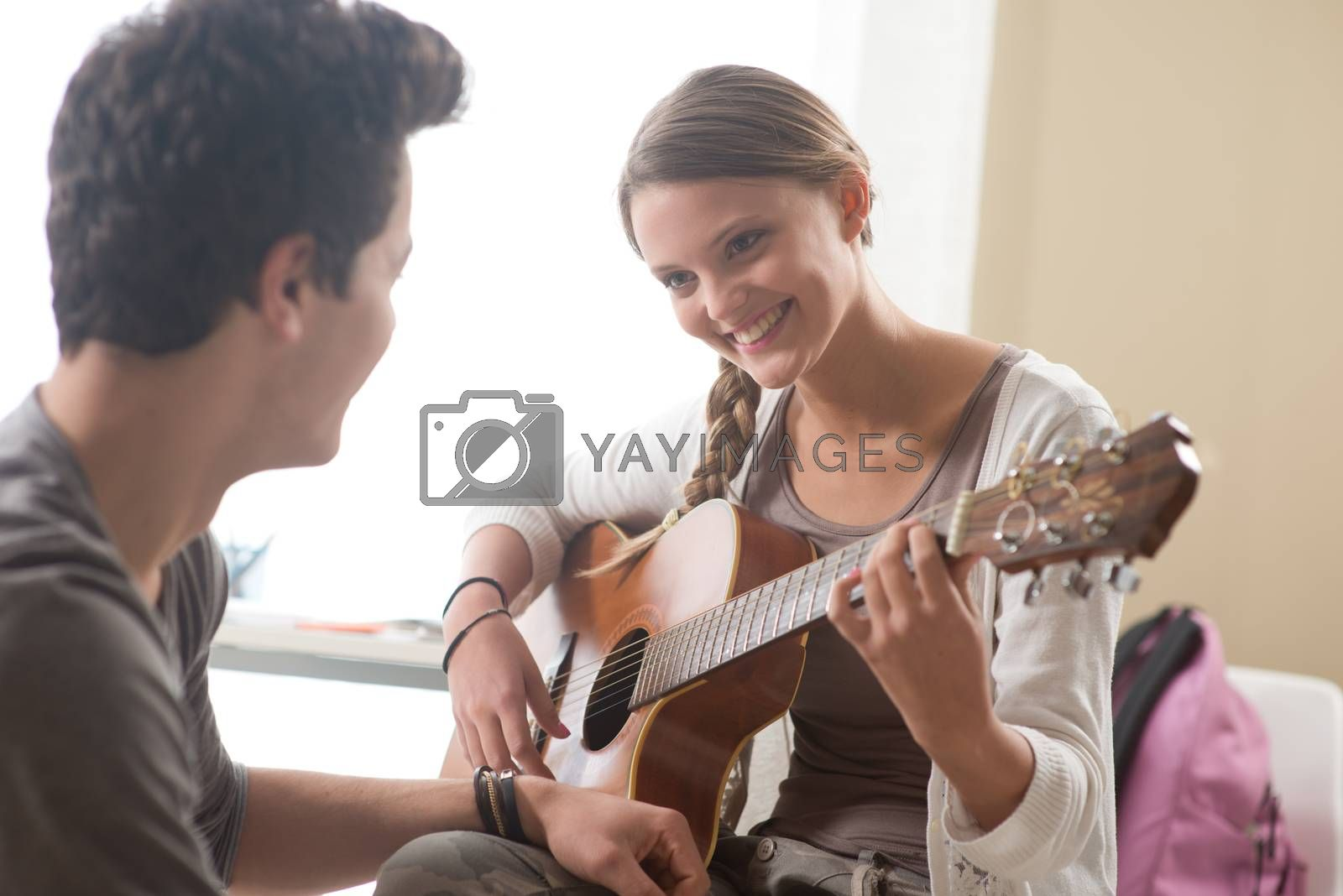 Beautiful girl playing guitar for her boyfriend at home