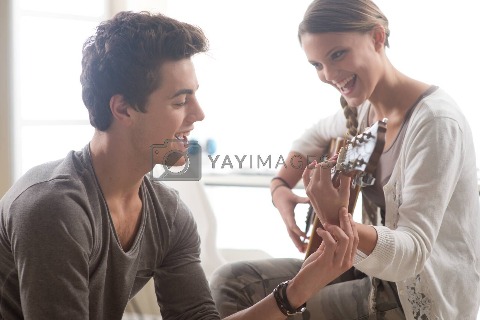 Young beautiful couple resting at home and playing guitar