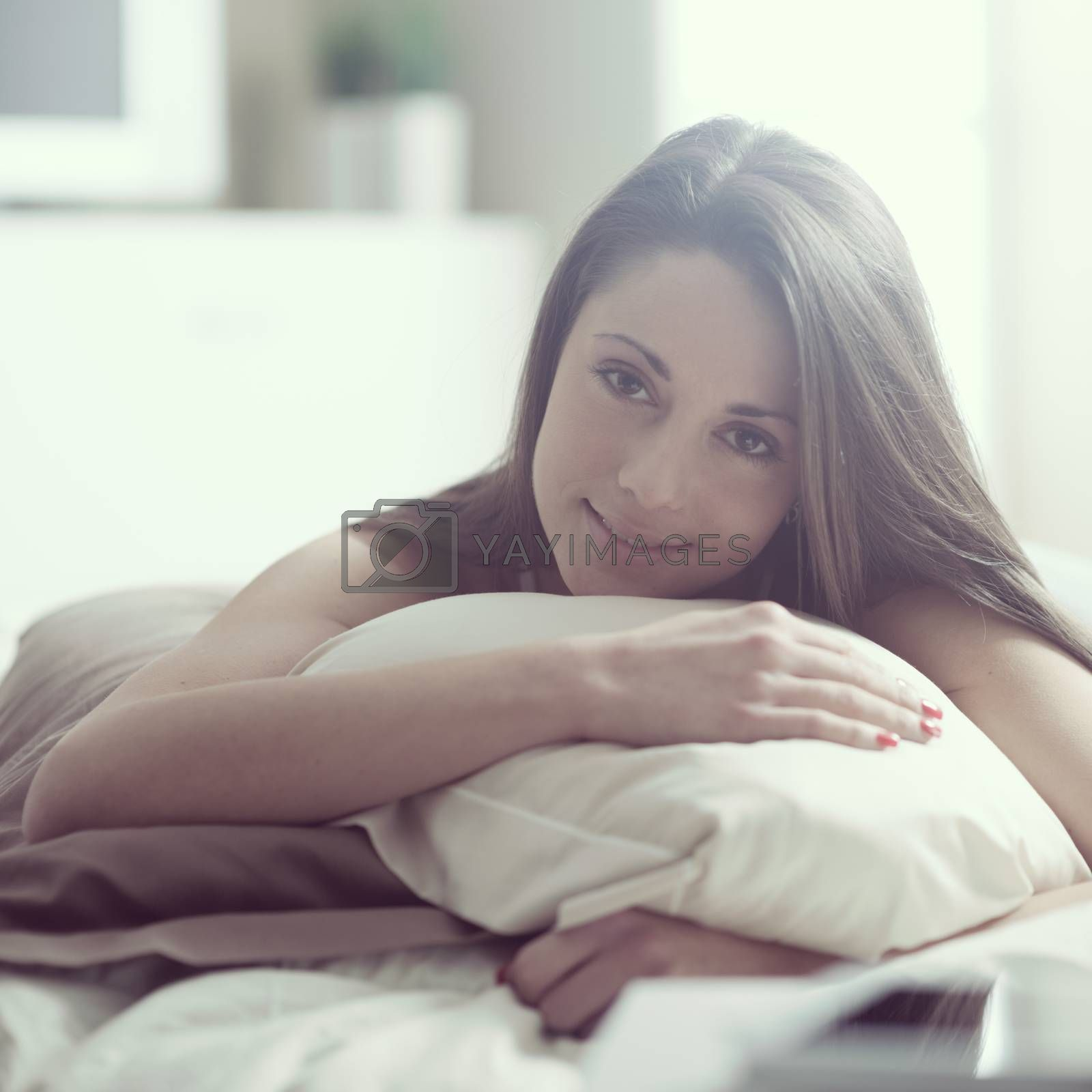 A gorgeous young woman smiling while lying in bed