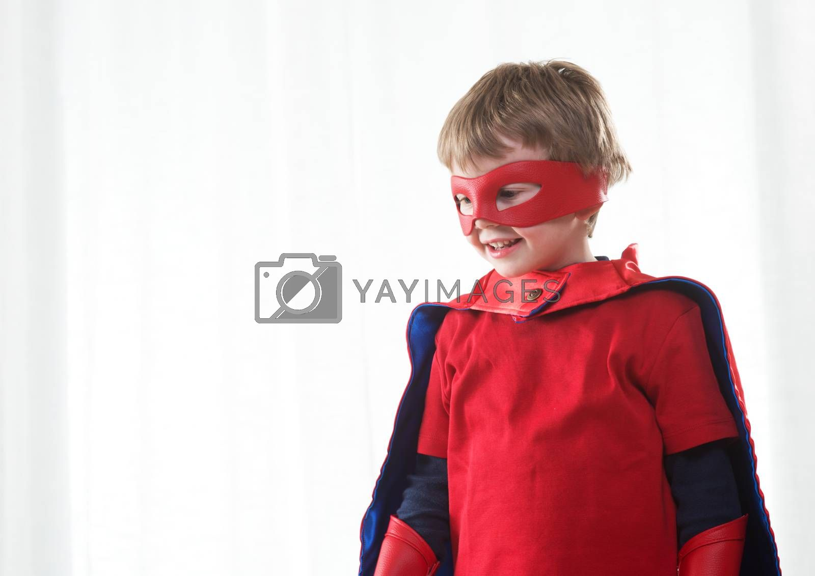 Smiling super hero kid with red mask and cape close up.