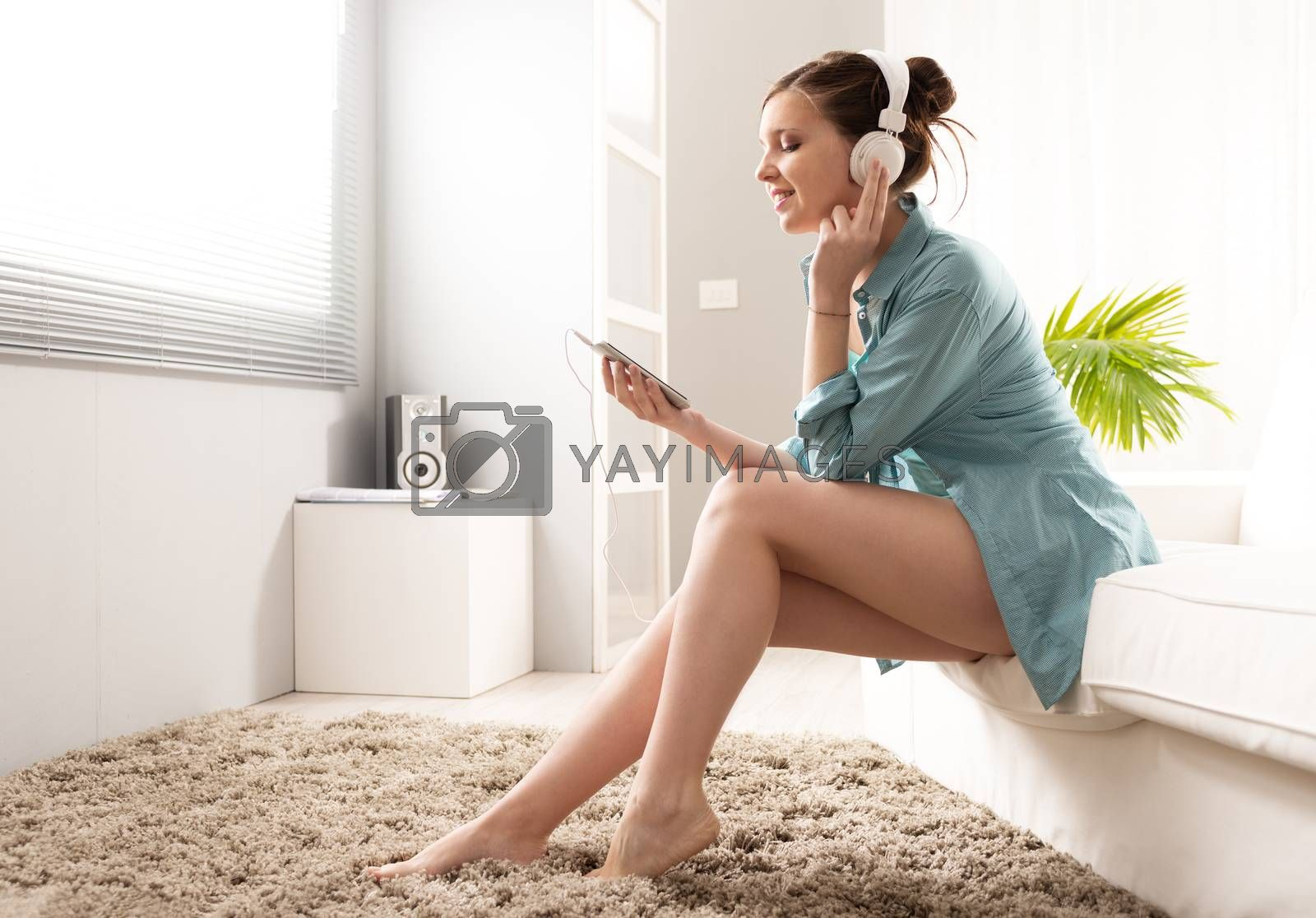 Girl listening to music on mp3 player with headphones.