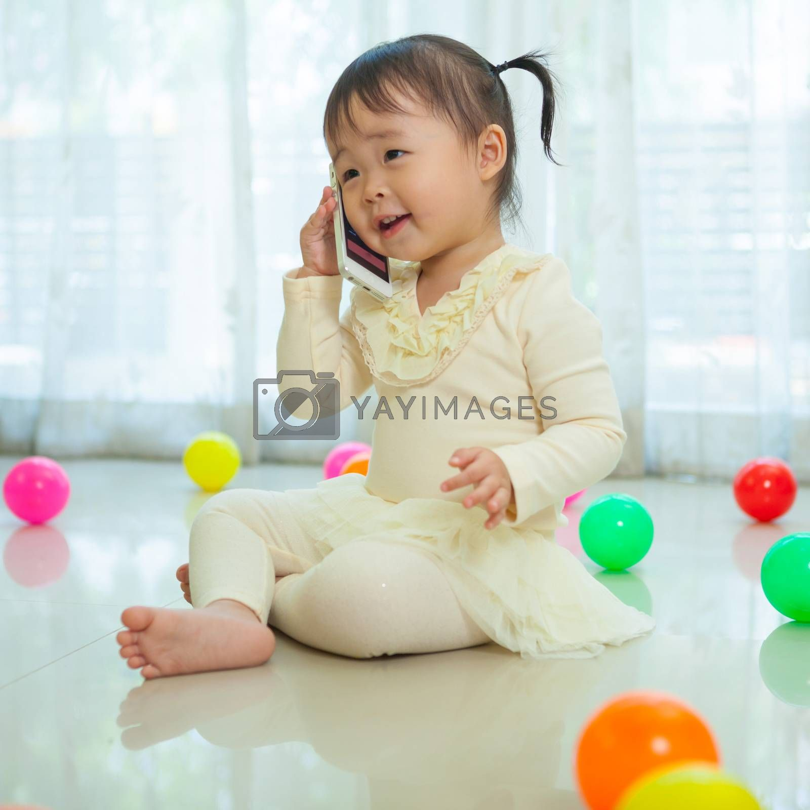 Portrait of pretty asian little girl talking on mobile phone