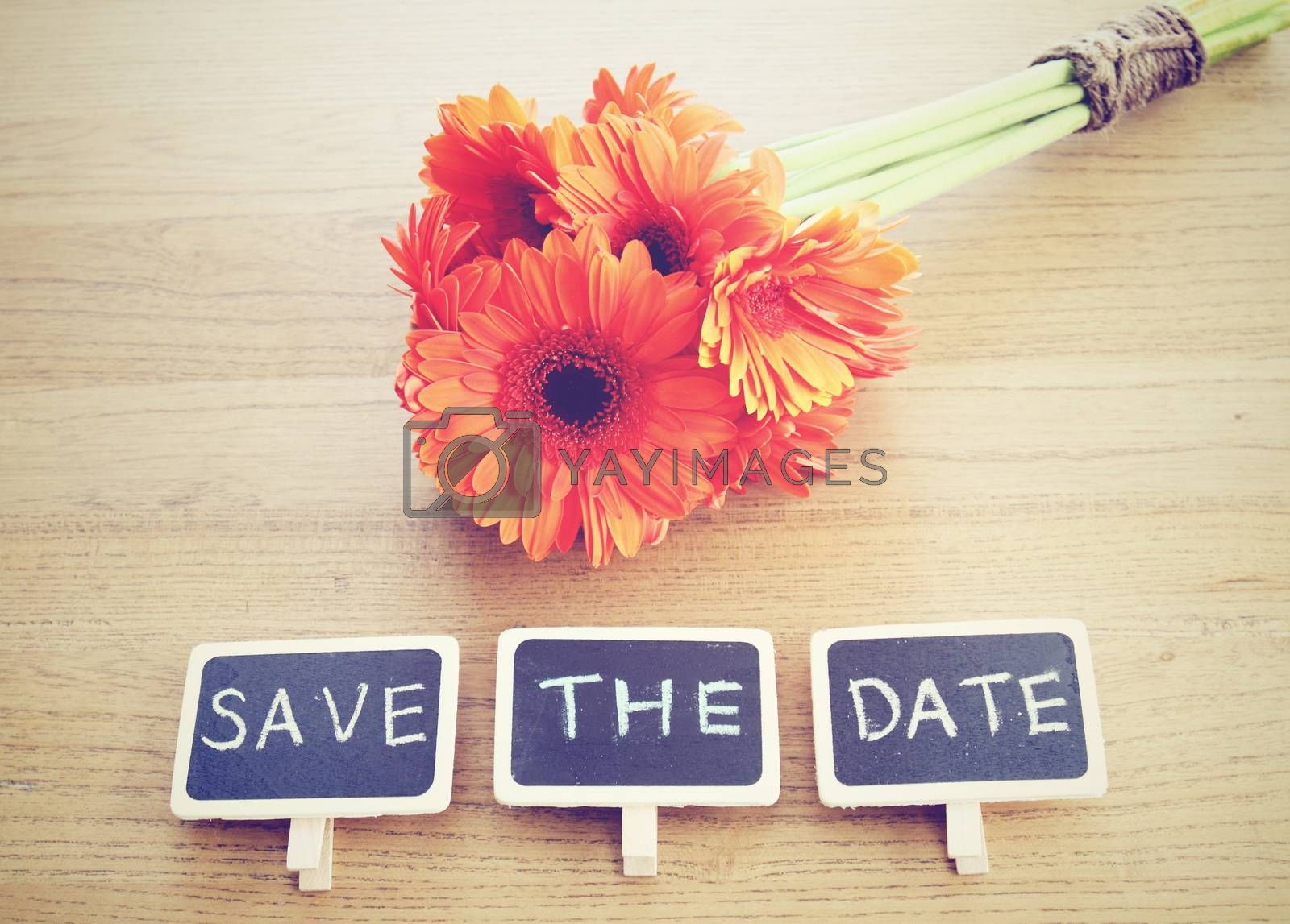 Save the date written on blackboard with flower, retro filter effect