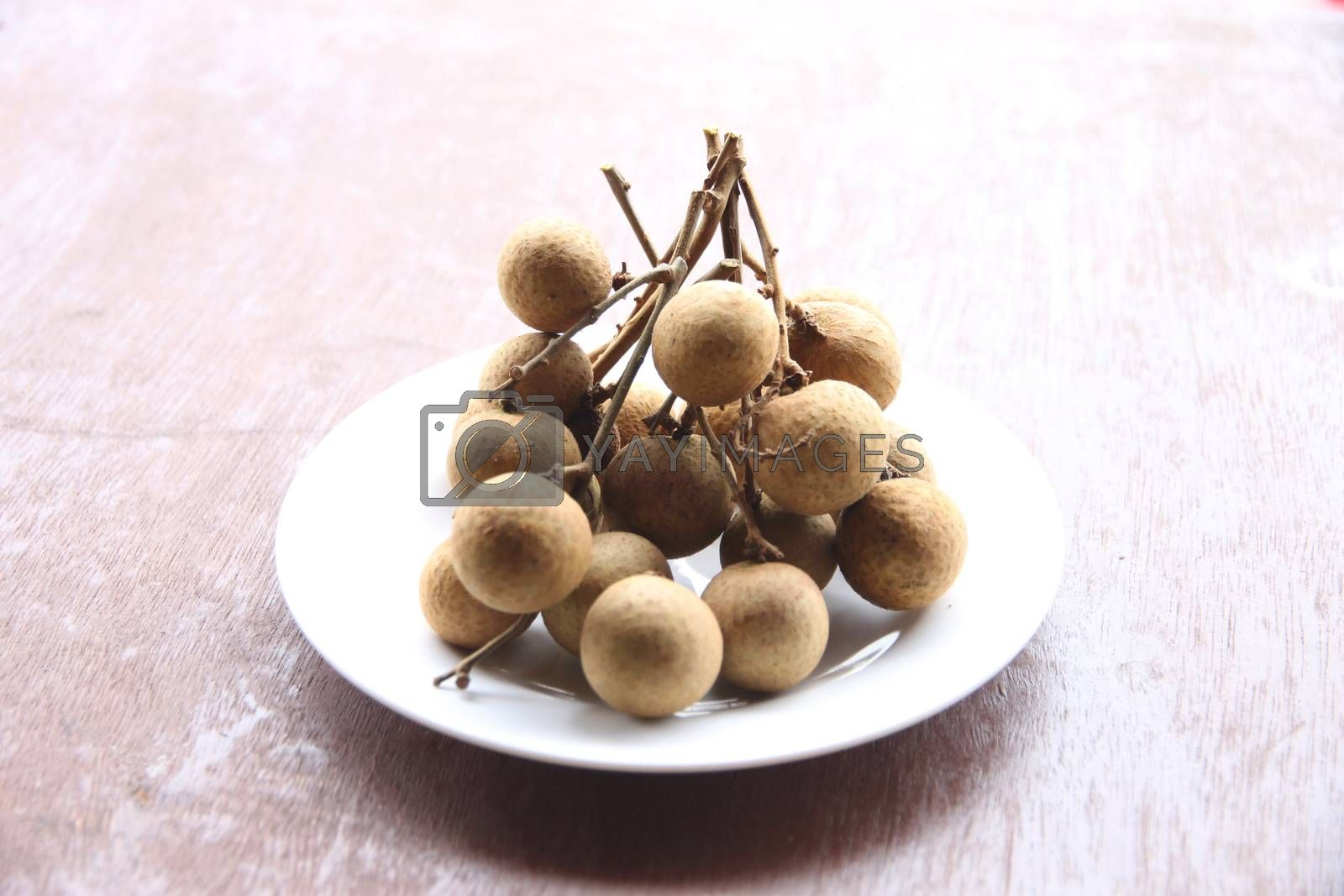 Fresh longan fruit in dish on the foods table.