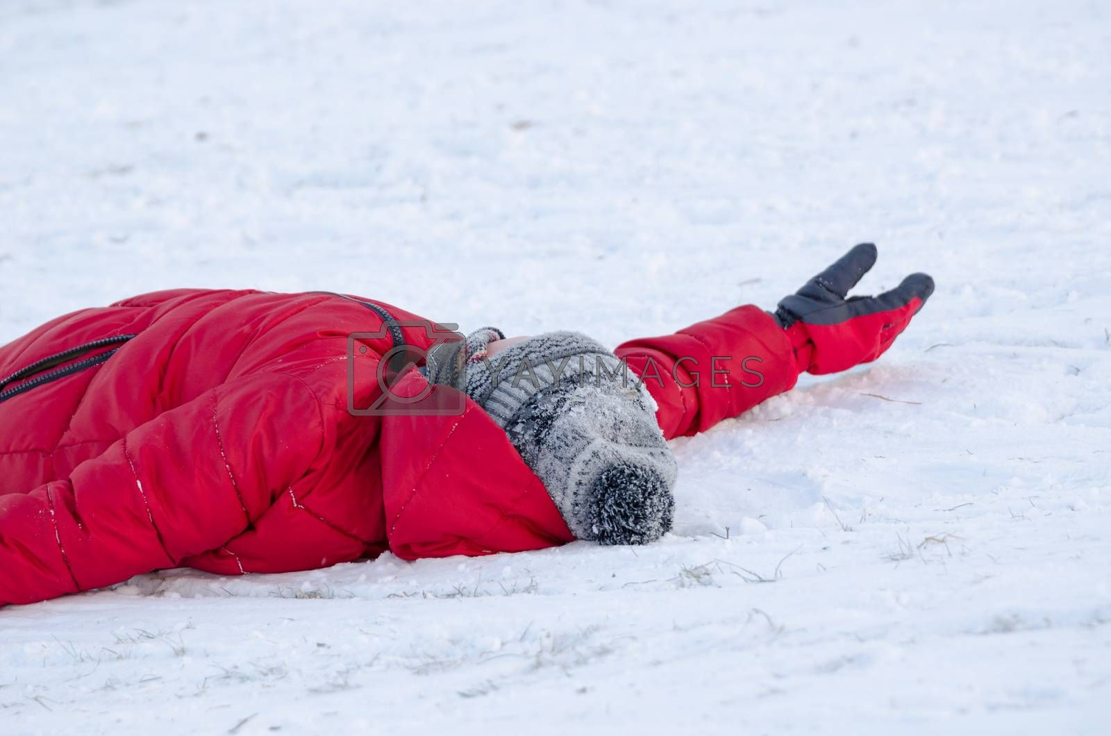child lie on snow with warm red feather jacket tired from slide outdoors, winter time leisure