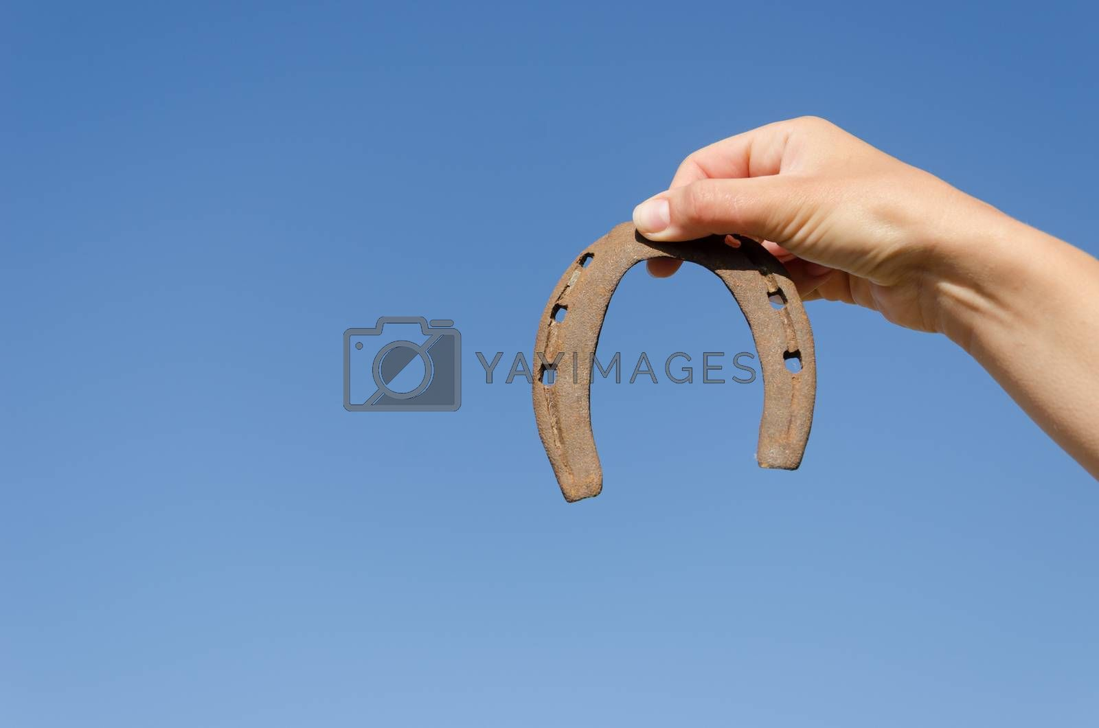 small rusty iron horseshoe in woman hand on blue sky bckground