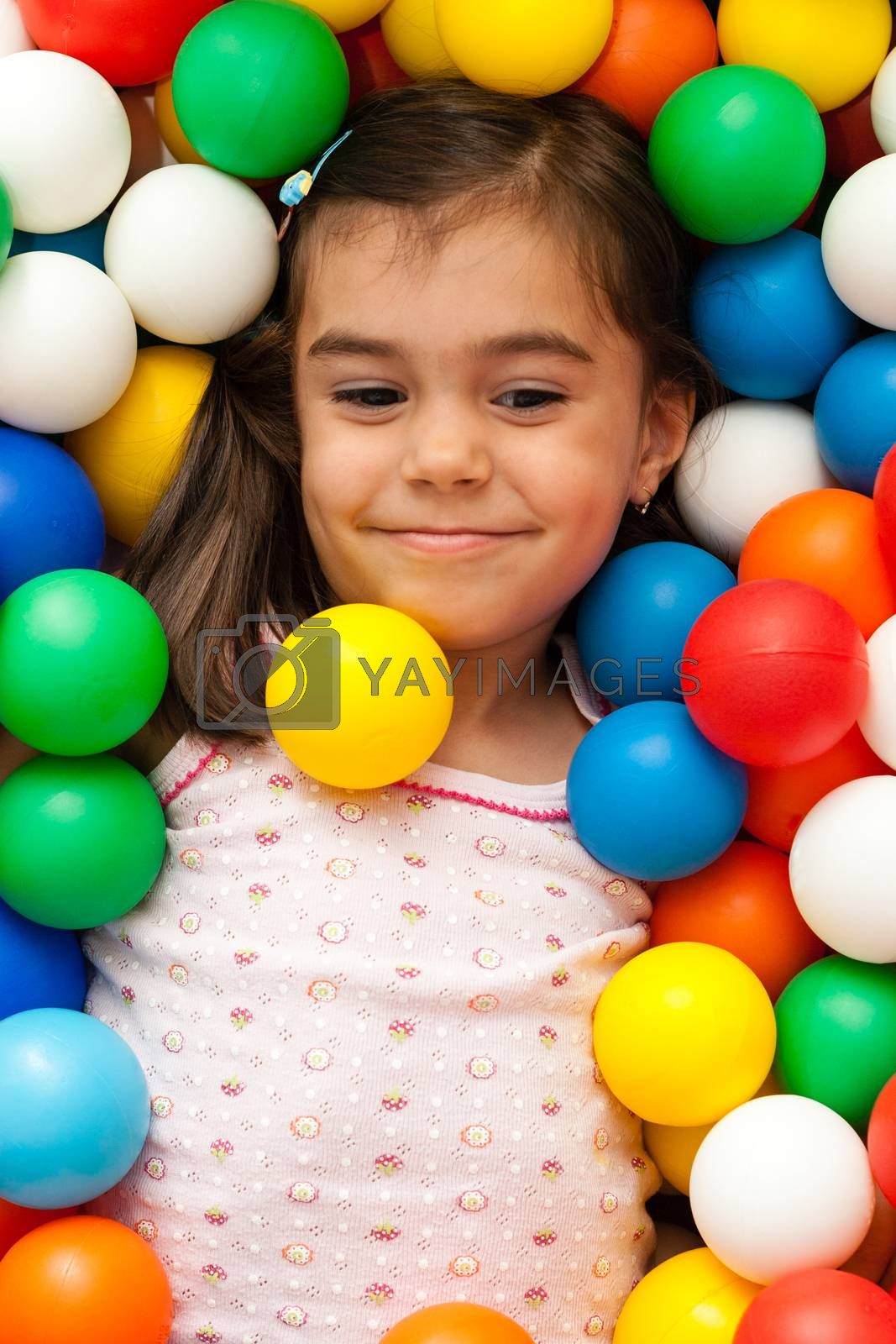 young girl playing with color toy balls