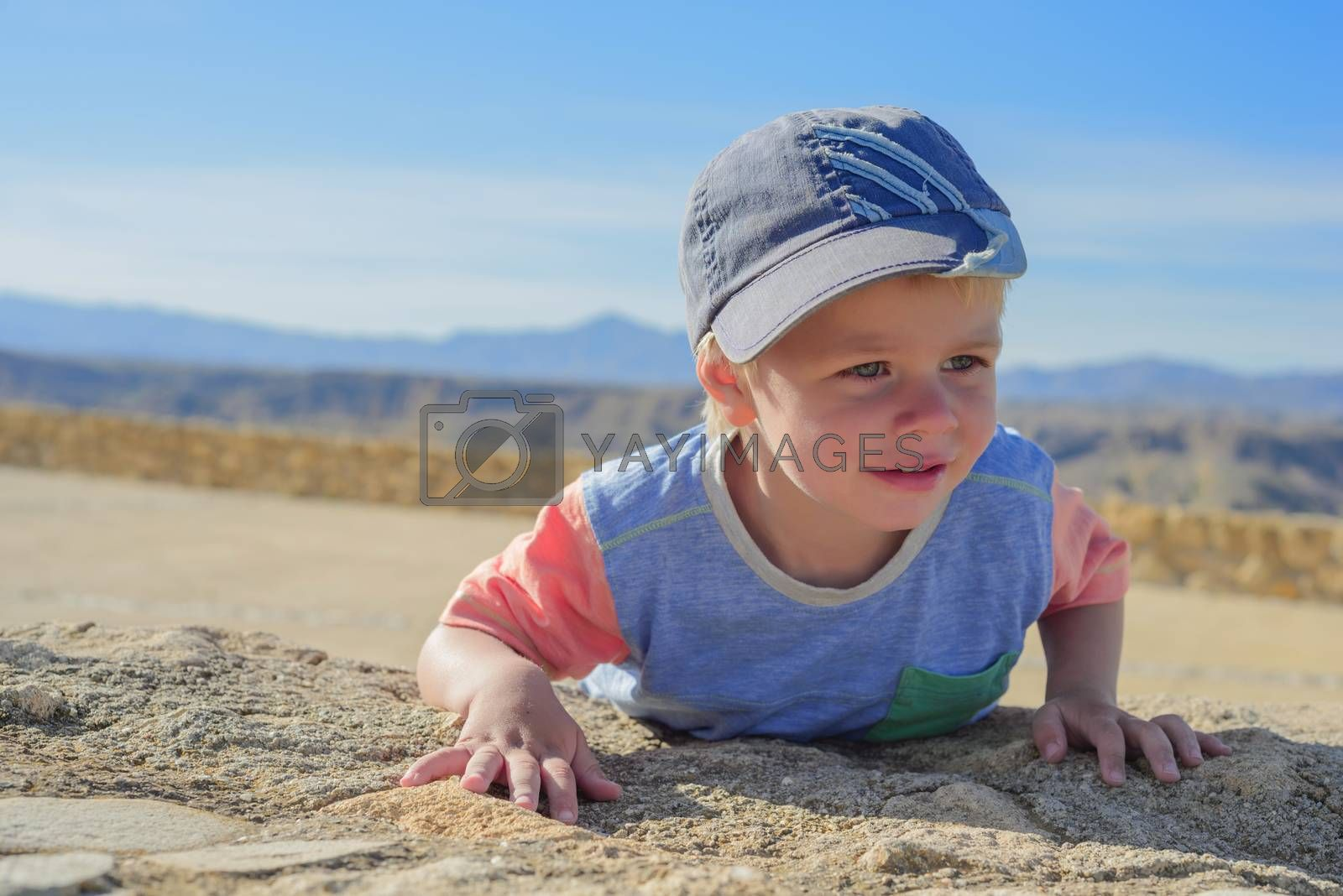 Cute little boy laying down on the rock